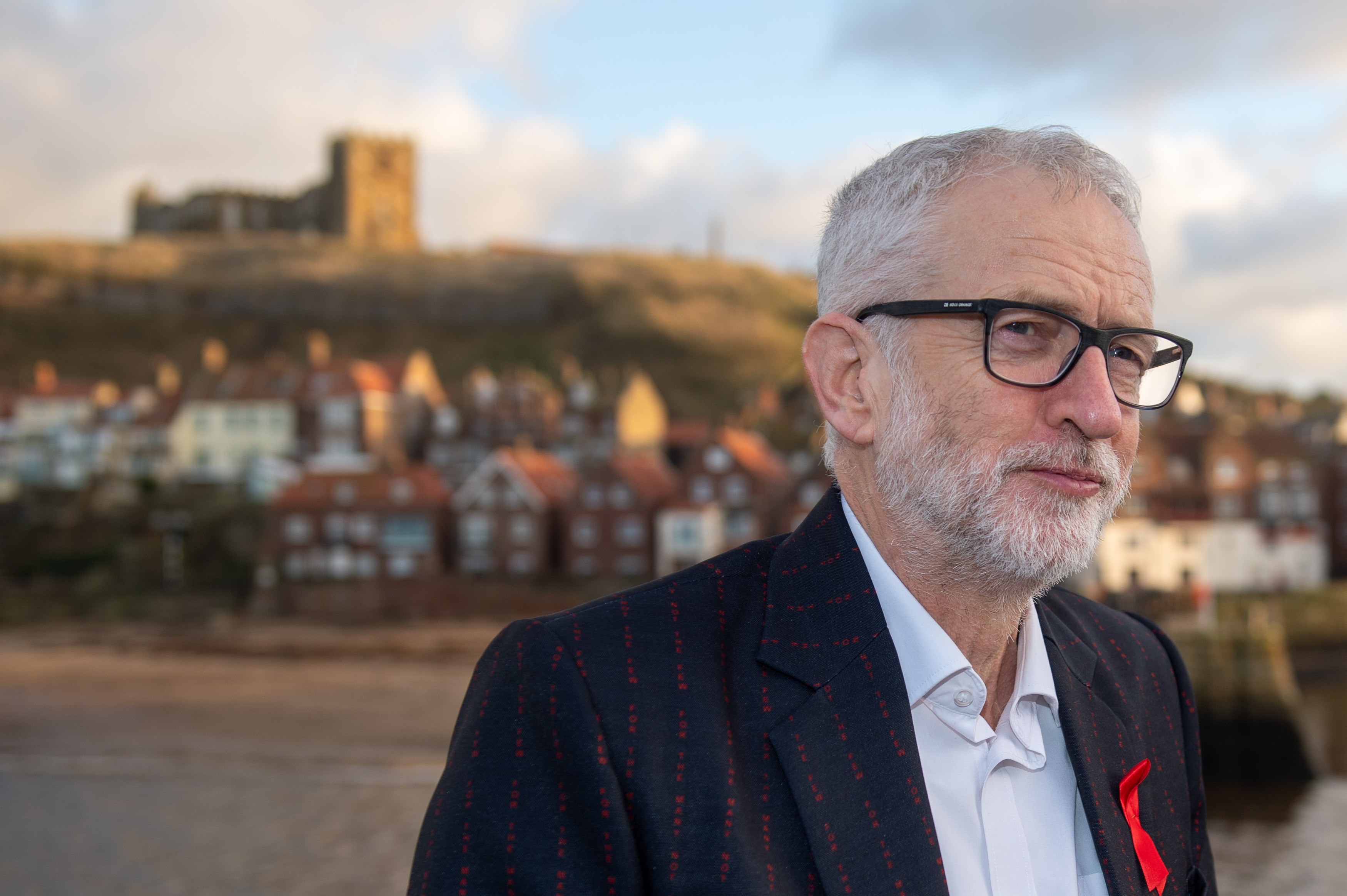 """Labour leader Jeremy Corbyn wearing a jacket that has """"for the many not the few"""" printed all over it, while on the General Election campaign trail in Whitby."""
