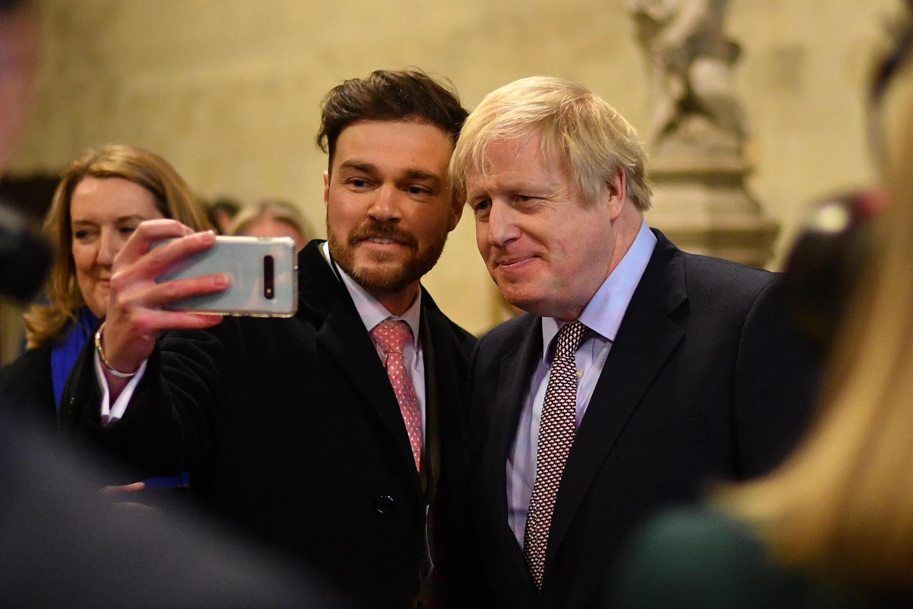 Prime Minister Boris Johnson poses for photographs as he welcomes the newly elected Conservative MPs at the Houses of Parliament in Westminster, London, after the party gained an 80-seat majority in the General Election.