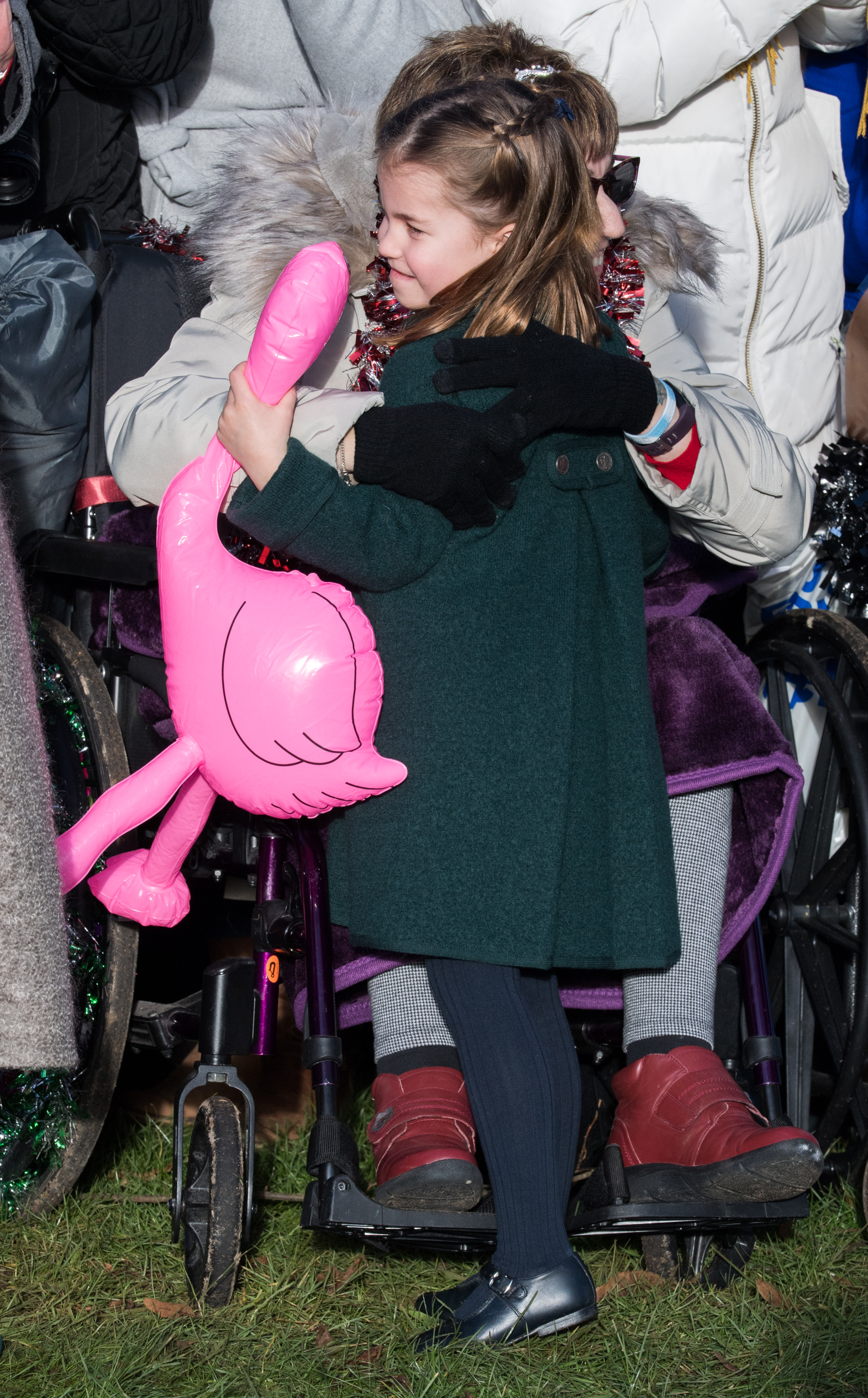 KING'S LYNN, ENGLAND - DECEMBER 25: Princess Charlotte of Cambridge is given a hug by a wellwisher as she attends the Christmas Day Church service at Church of St Mary Magdalene on the Sandringham estate on December 25, 2019 in King's Lynn, United Kingdom. (Photo by Pool/Samir Hussein/WireImage)