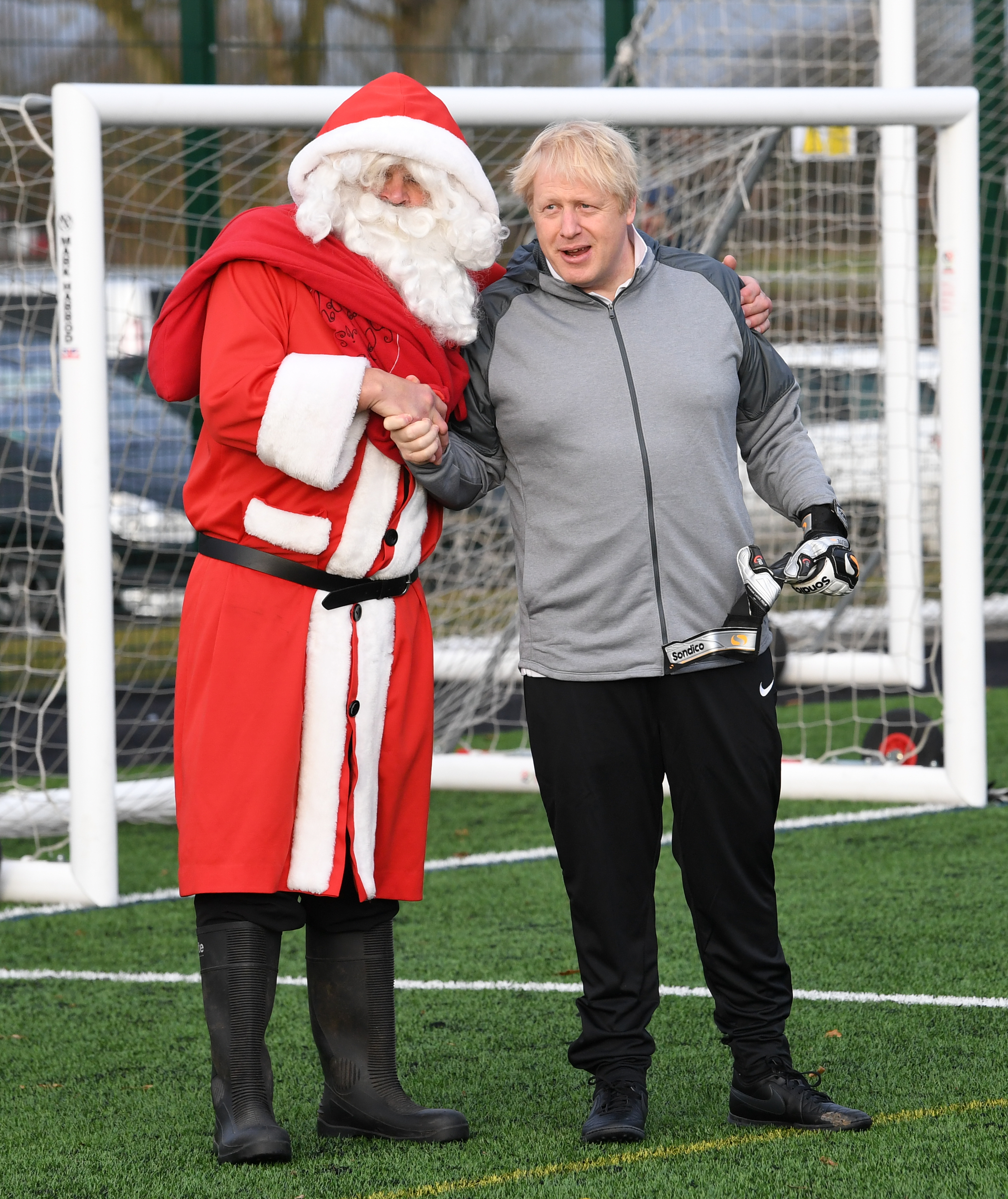 Prime Minister Boris Johnson with a man dressed as Father Christmas before a football match between Hazel Grove Utd and Poynton Jnr u10s in the Cheshire Girls football league in Cheadle Hume, Cheshire, while on the election campaign trail.