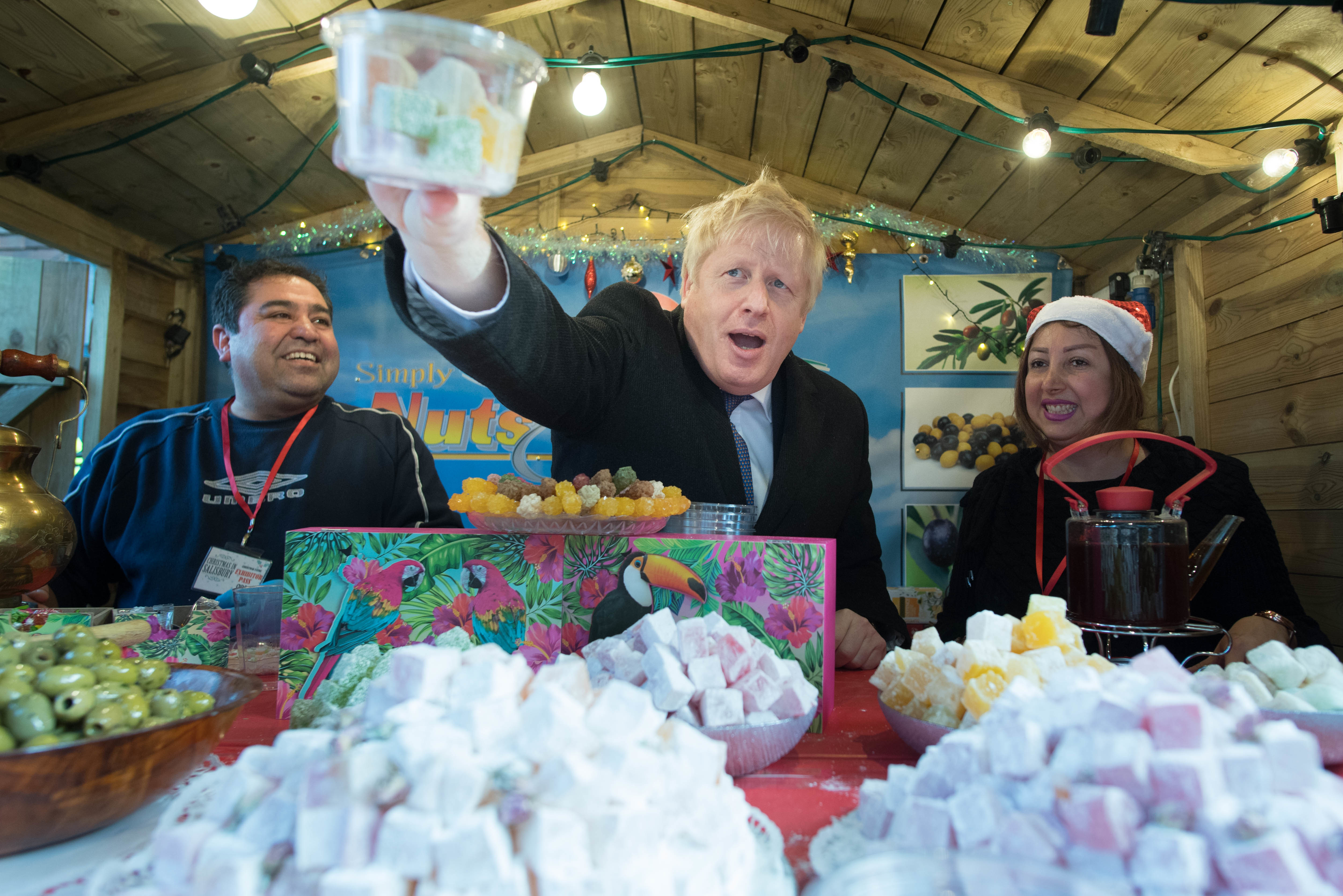 Prime Minister Boris Johnson helps to serve customers at a Turkish delight stall at a Christmas market in Salisbury today whilst on the General Election campaign trail in Wiltshire. PA Photo. Picture date: Tuesday December 3, 2019. See PA story POLITICS Election. Photo credit should read: Stefan Rousseau/PA Wire