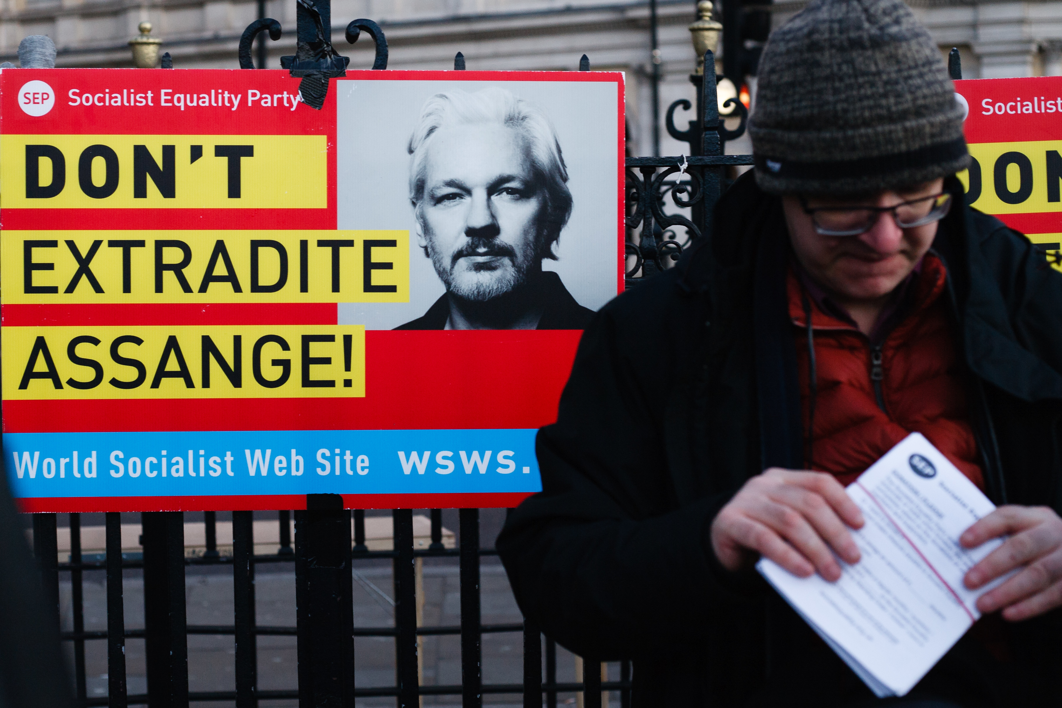 An activist stands next to a poster opposing extradition of Wikileaks founder, Julian Assange during the demonstration. President Trump arrived in the UK on a three-day visit last night, chiefly to attend the NATO summit in Watford. Activists protest against Trump�s visit in Trafalgar Square. (Photo by David Cliff / SOPA Images/Sipa USA)