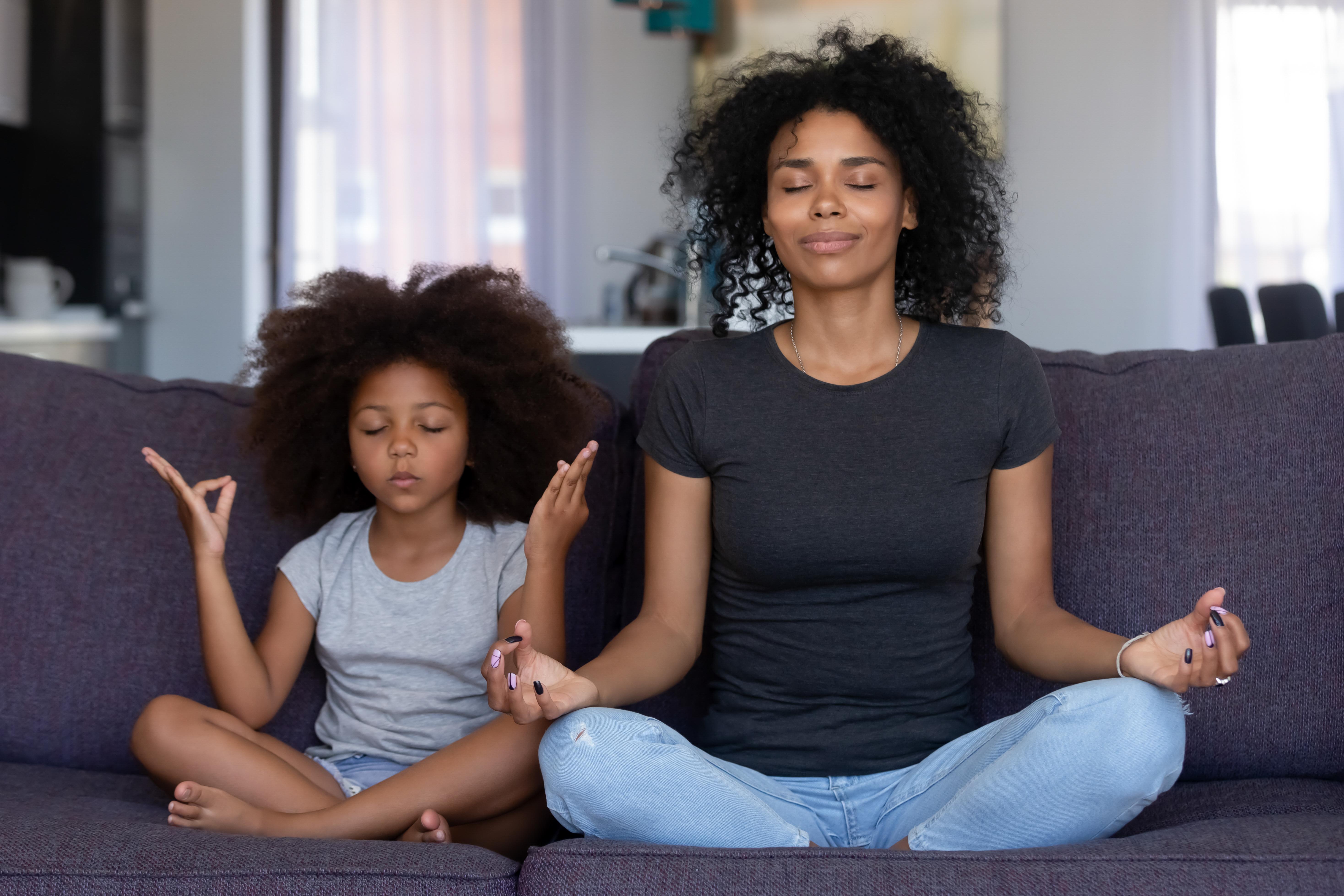 Uma mulher adulta e uma criança sentadas lado a lado em um sofá de cor escura, fazendo meditação de olhos fechados com expressão facial relaxada e concentrada.