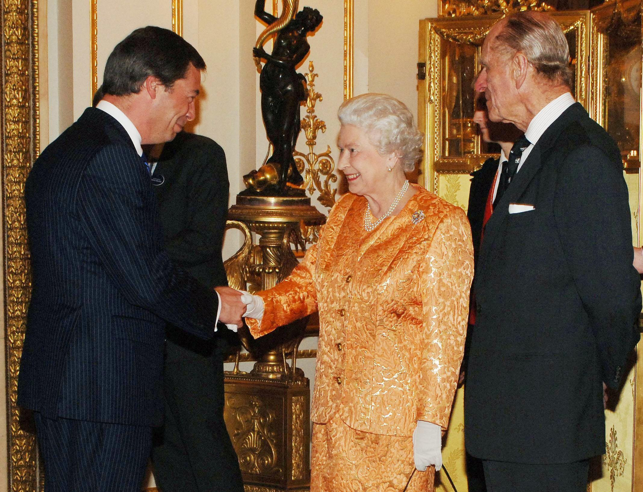 Britain's Queen Elizabeth II and the Duke of Edinburgh (right) host a Buckingham Palace reception for backbench MPs, including Independent Party leader and MEP Nigel Farage (left).