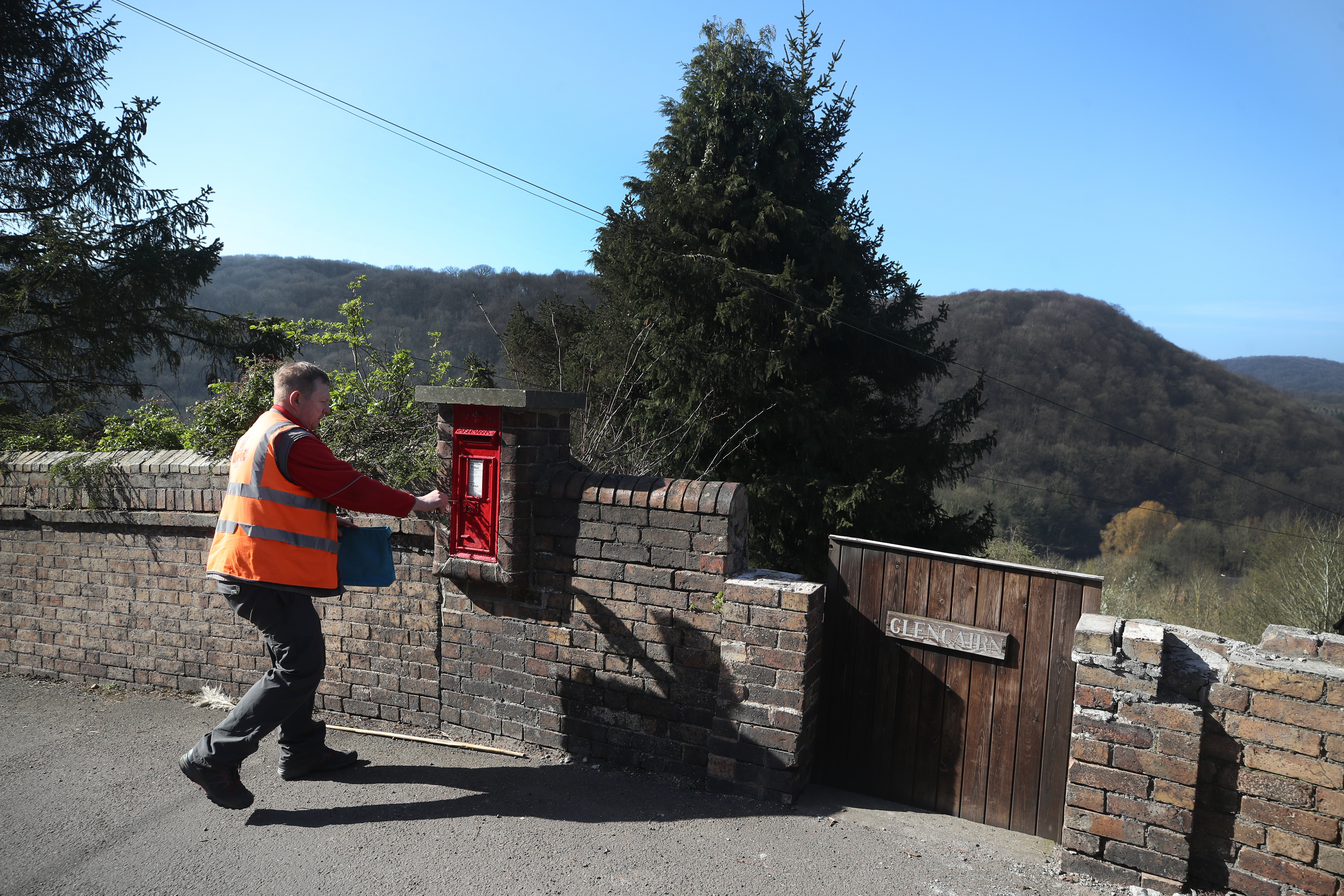 Postal delivery worker Matt delivers mail in the village of Ironbridge in Shropshire, while his customers have to stay at home, after Prime Minister Boris Johnson has put the UK in lockdown to help curb the spread of the coronavirus.