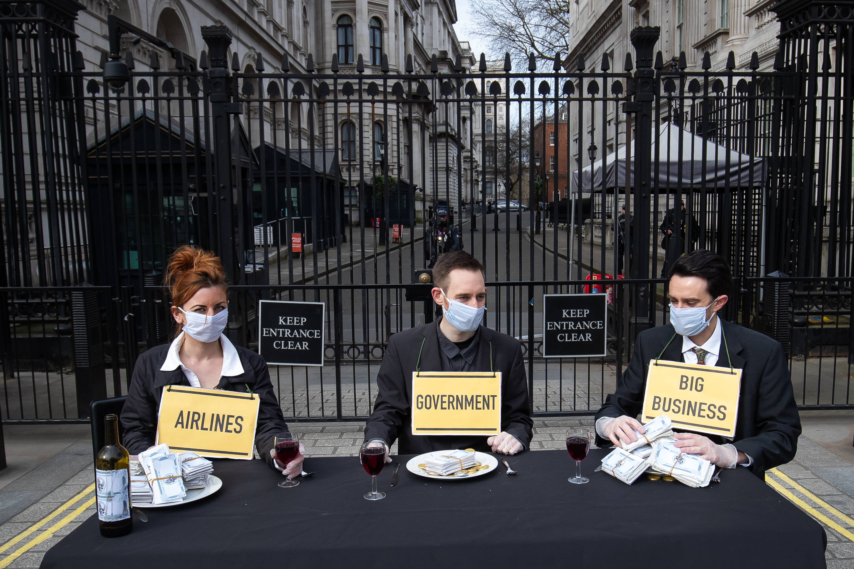 Protesters from a group called 'Pause the System' wear face masks as they demonstrate outside Downing Street in London. The group are calling for greater action from the government as the UK's coronavirus death toll reached 144 as of 1pm on Thursday, with around four in 10 of all deaths so far in London.