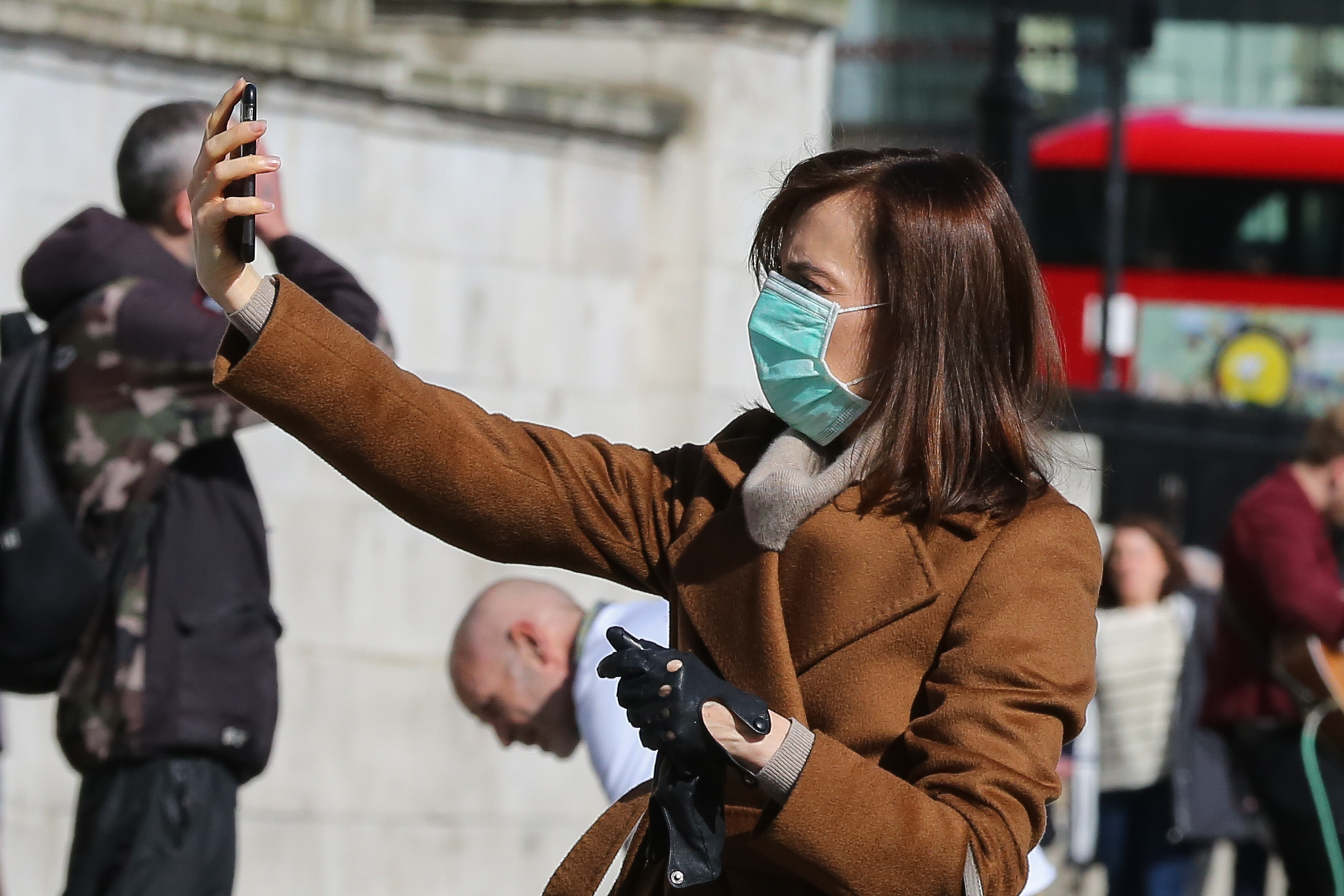 A woman wearing a face mask as a precaution against the spread of Coronavirus takes a selfie in central. (Photo by Steve Taylor / SOPA Images/Sipa USA)