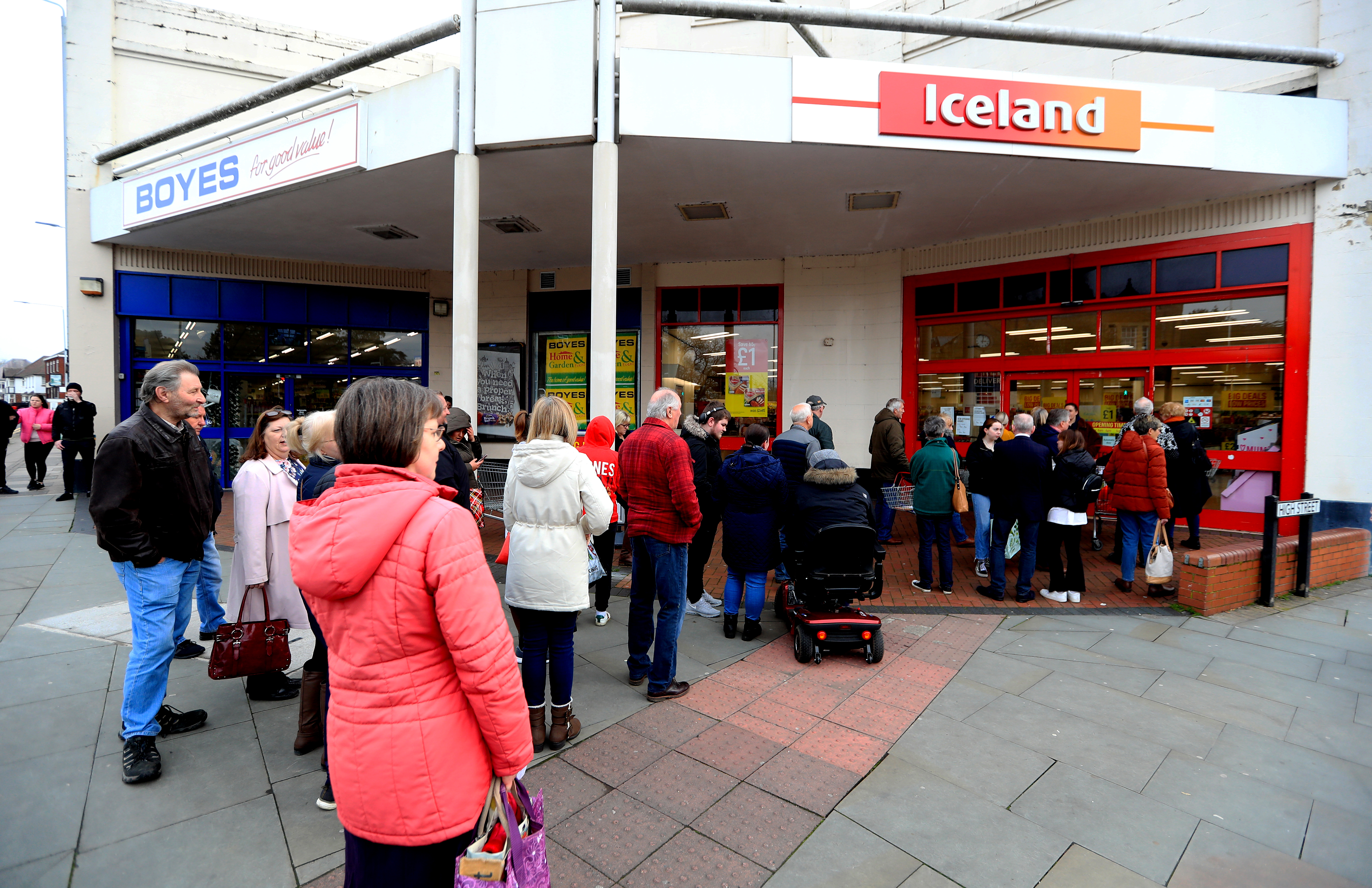 People are seen queueing up outside an Iceland at Melton Mowbray Market after NHS England announced that the coronavirus death toll had reached 104 in the UK.