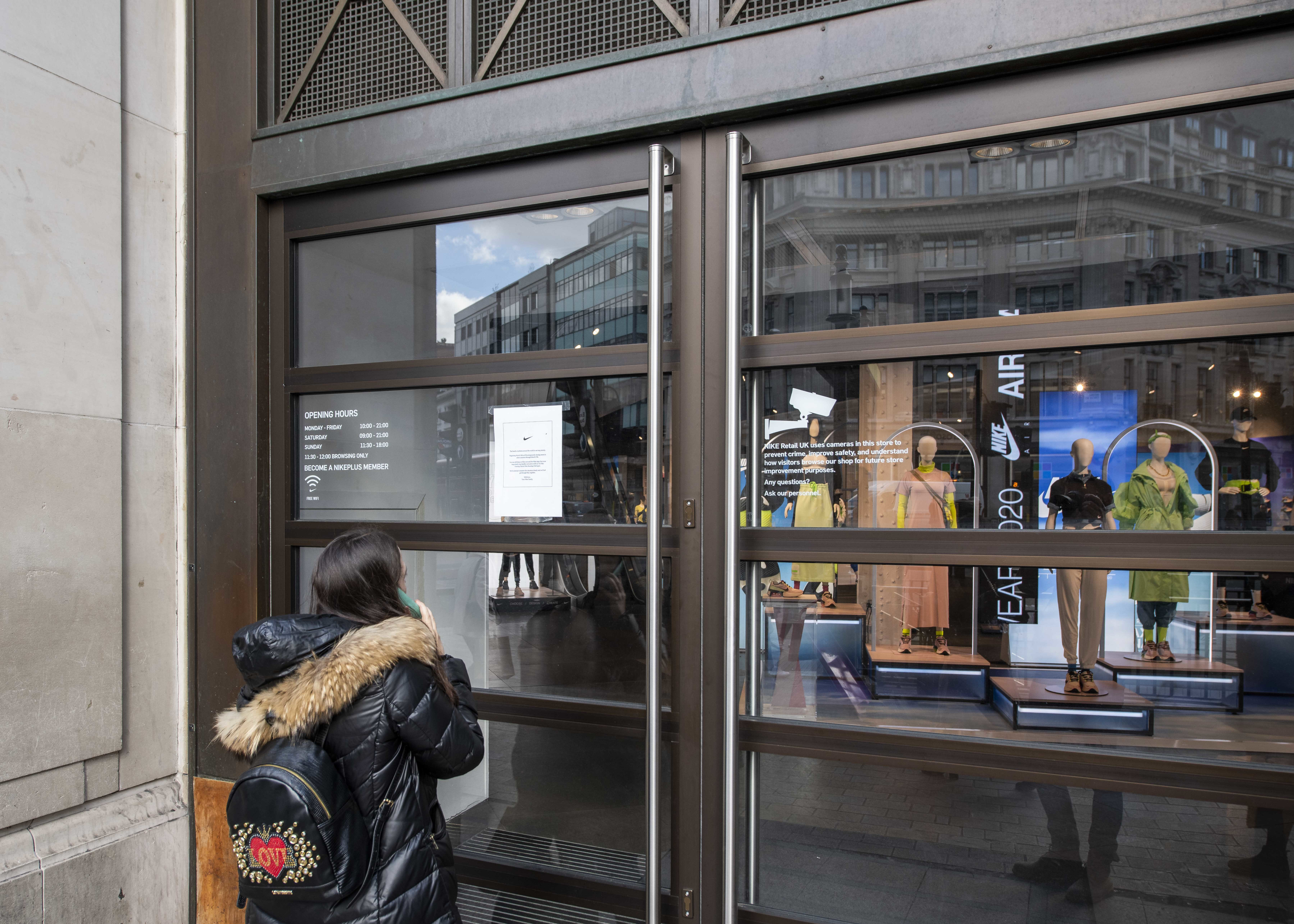 A shopper reads a closure sign on the doors of Niketown in Oxford Circus which closed due to the Coronavirus, Oxford Road, London.  Picture date: Monday 16th March 2020.  Photo credit should read:  David Jensen/ EMPICS Entertainment