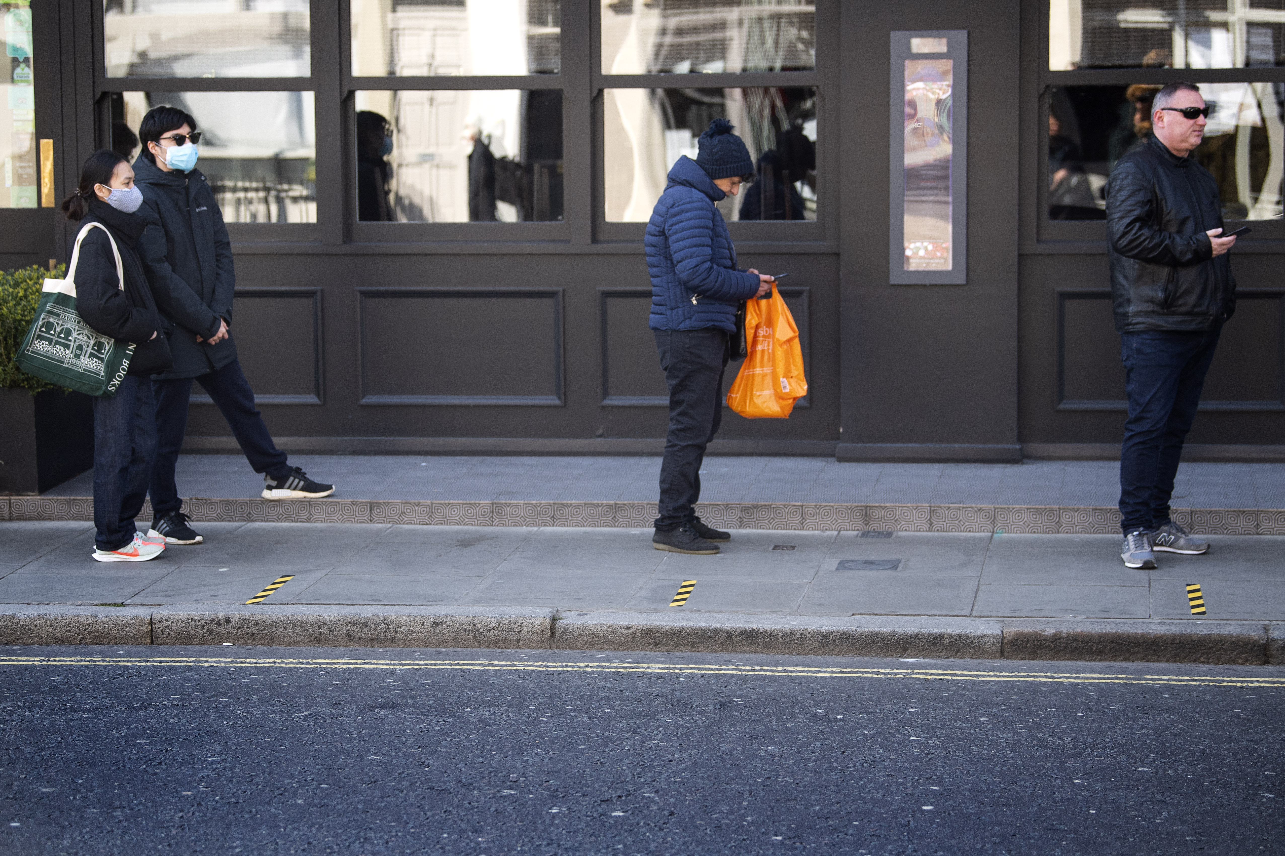 Customers queue between social distancing markers on the pavement outside a supermarket in Westminster, London after Prime Minister Boris Johnson put the UK in lockdown to help curb the spread of the coronavirus.