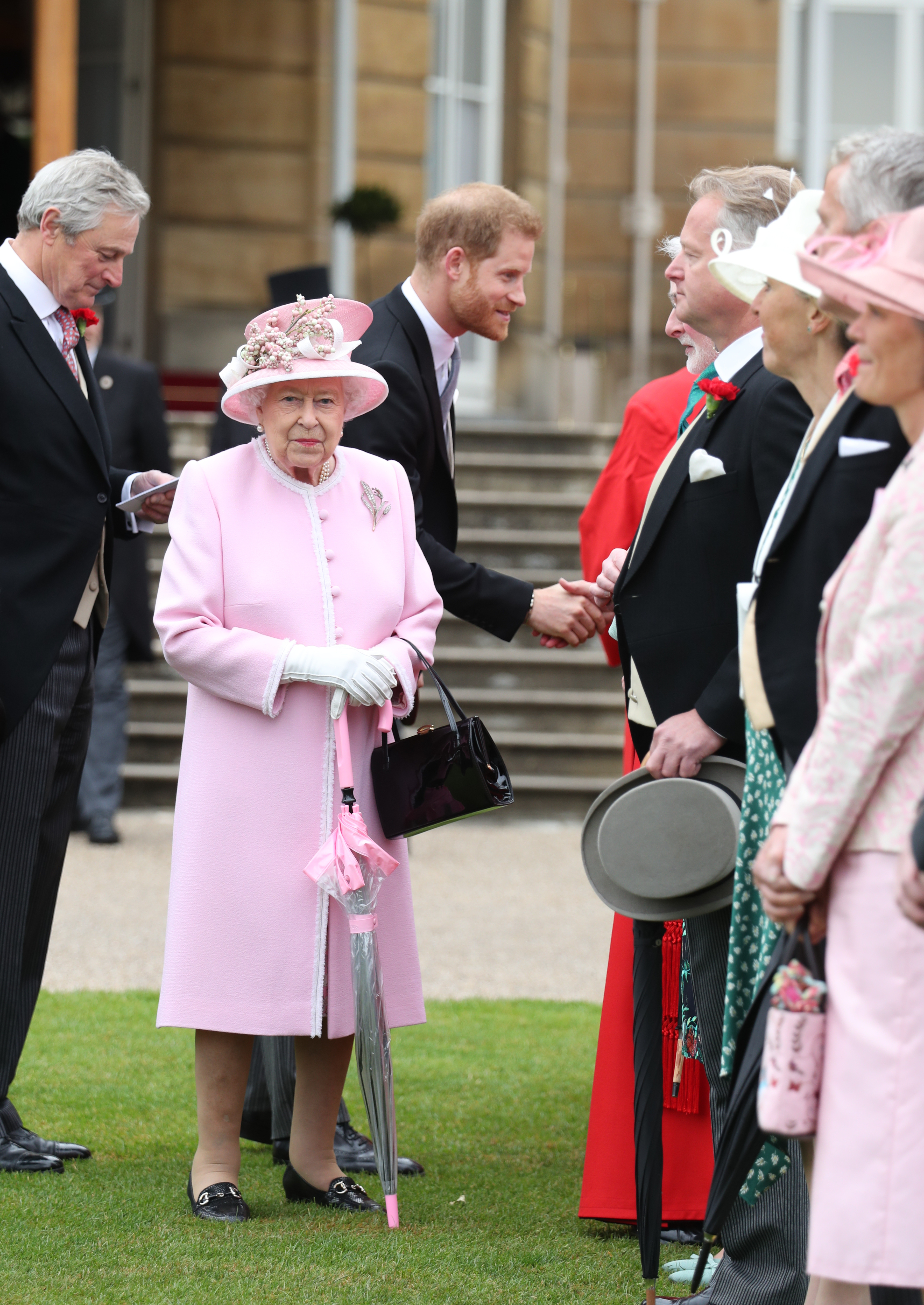Queen Elizabeth II and the Duke of Sussex meet guests during a Royal Garden Party at Buckingham Palace in London.