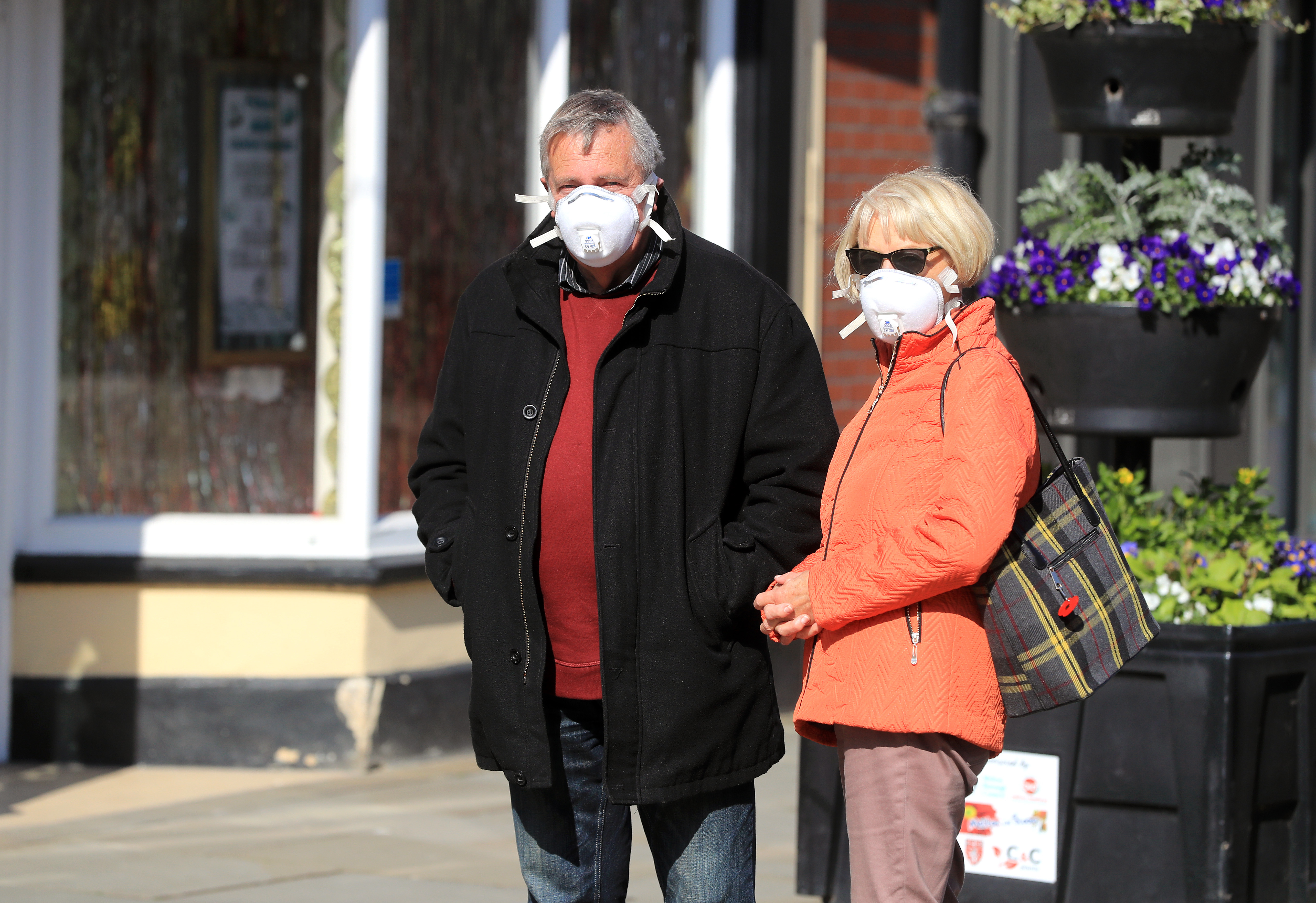 Members of the public wearing masks queue to enter shops in Melton Mowbray as the UK continues in lockdown to help curb the spread of the coronavirus.