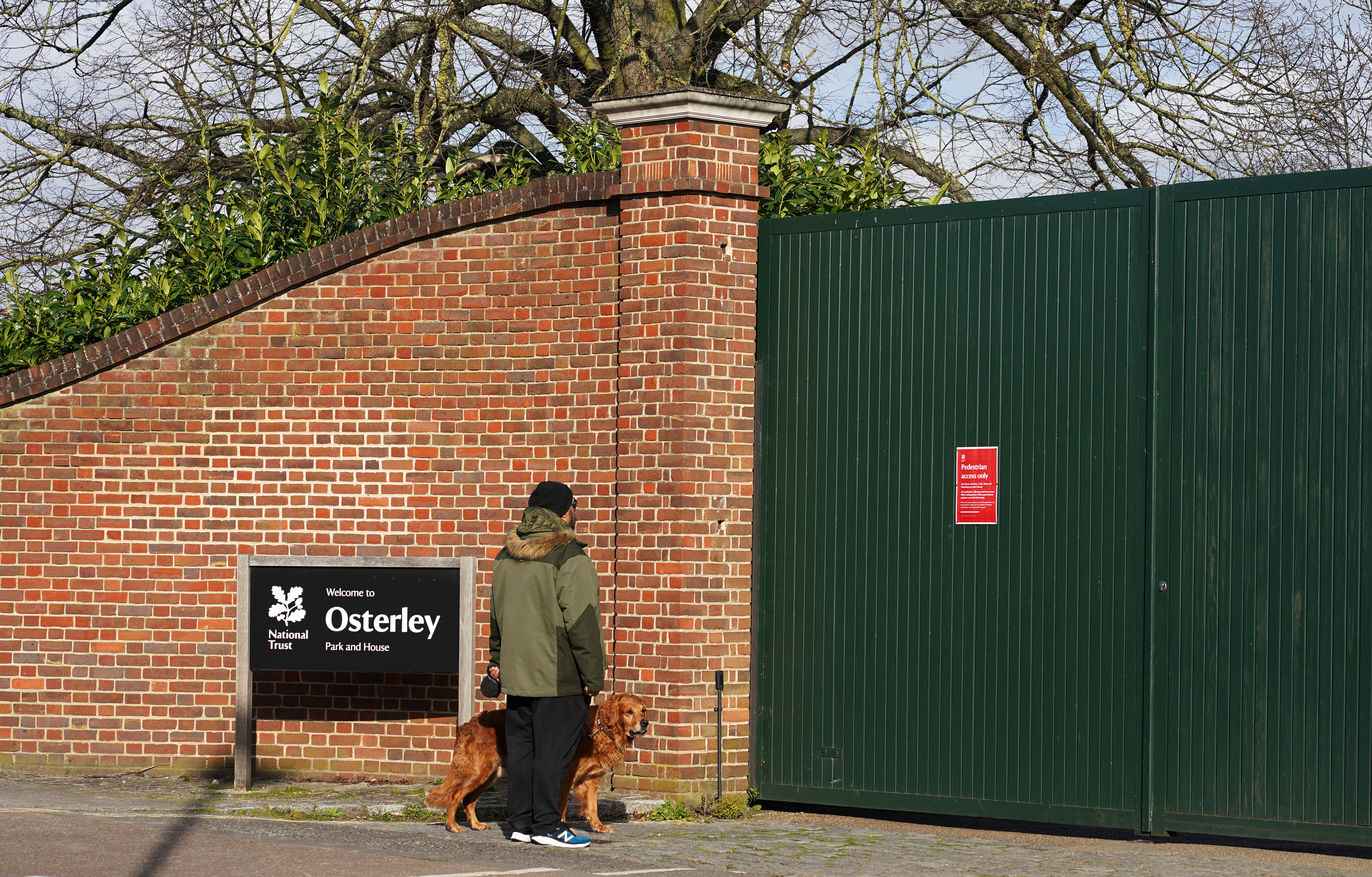 A dog walker looks at the signage the entrance for Osterley Park and House in Isleworth, London, after The National Trust announced it has shut down all of its parks and and gardens across the UK until further notice.