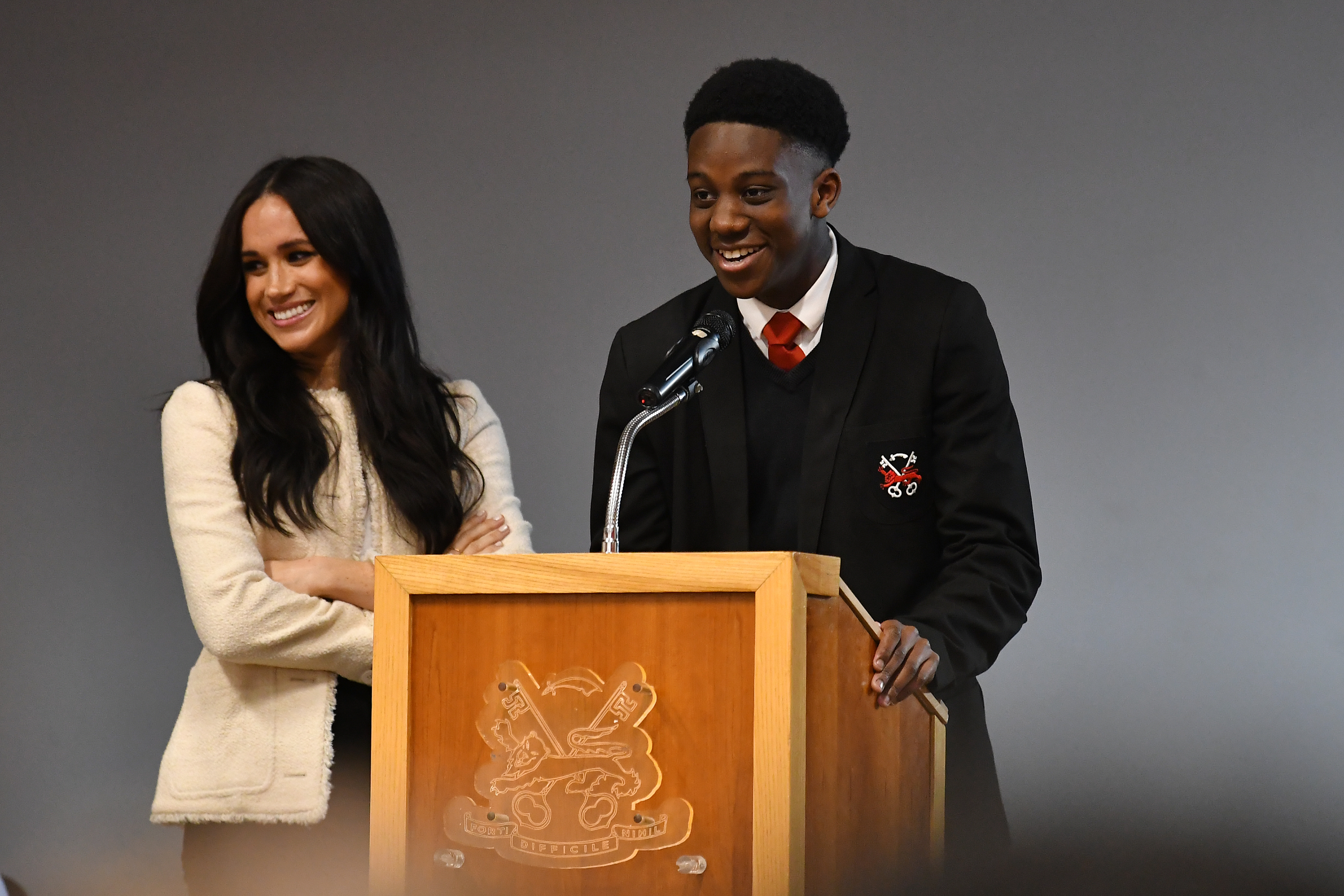 The Duchess of Sussex (left) smiles as head boy Aker Okoye, speaks in a school assembly, during her surprise visit to the Robert Clack Upper School in Dagenham, Essex, to celebrate International Women's Day.