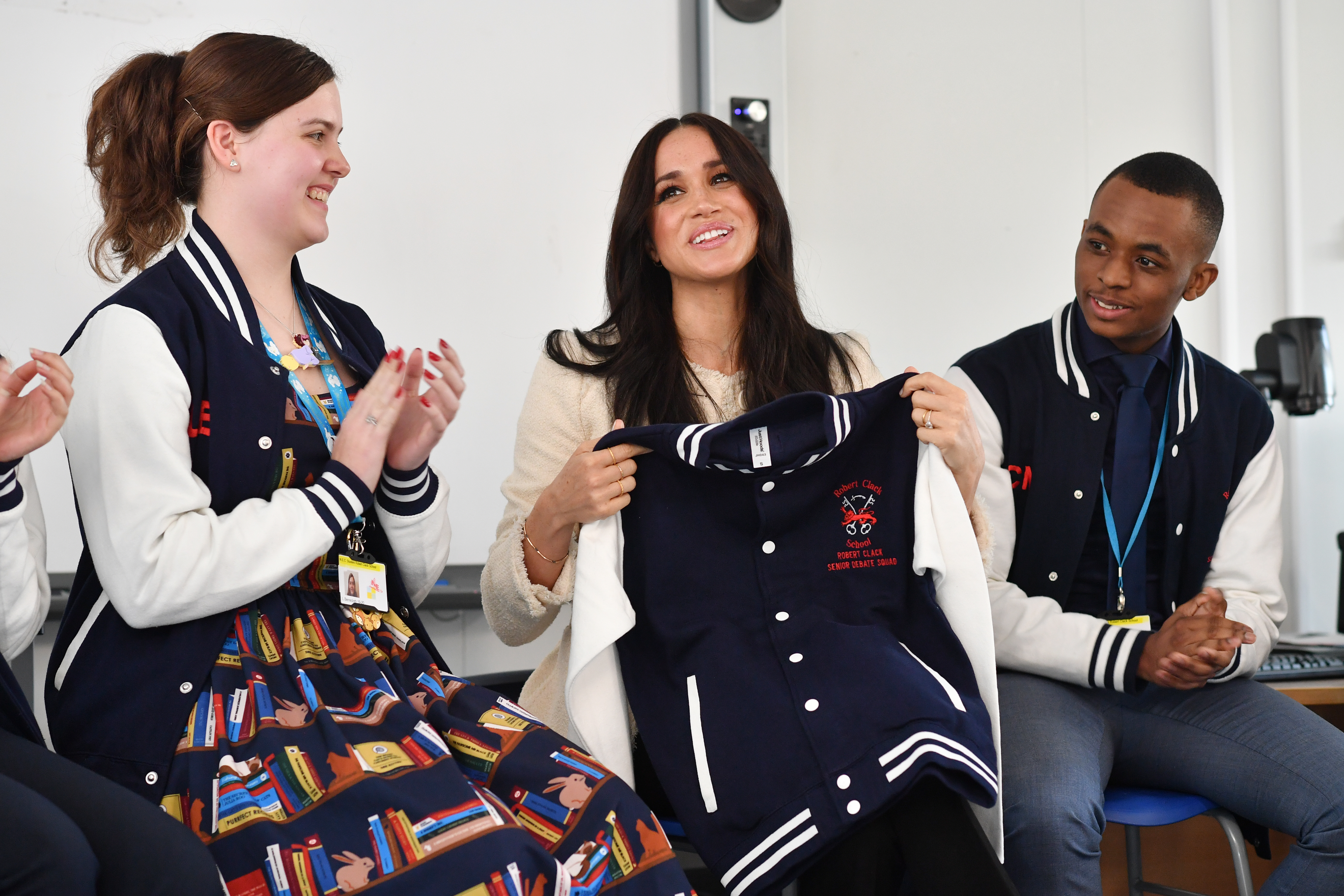 The Duchess of Sussex is presented with an item of school clothing as she joins in a discussion of the 'Senior Debate Squad' at the Robert Clack Upper School in Dagenham, Essex, during a surprise visit to celebrate International Women's Day.