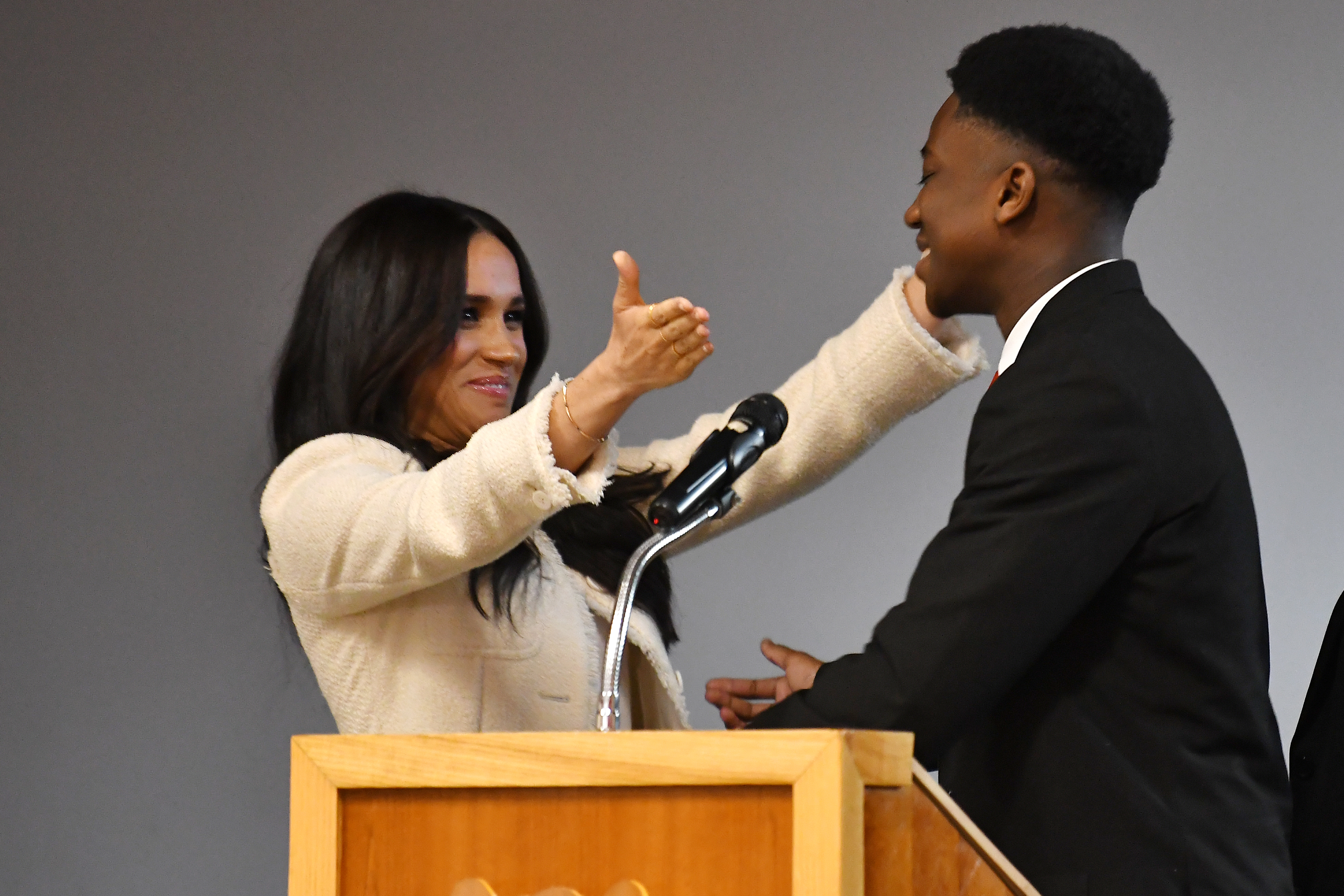 The Duchess of Sussex (left) embraces head boy Aker Okoye, in a school assembly, during her surprise visit to the Robert Clack Upper School in Dagenham, Essex, to celebrate International Women's Day.