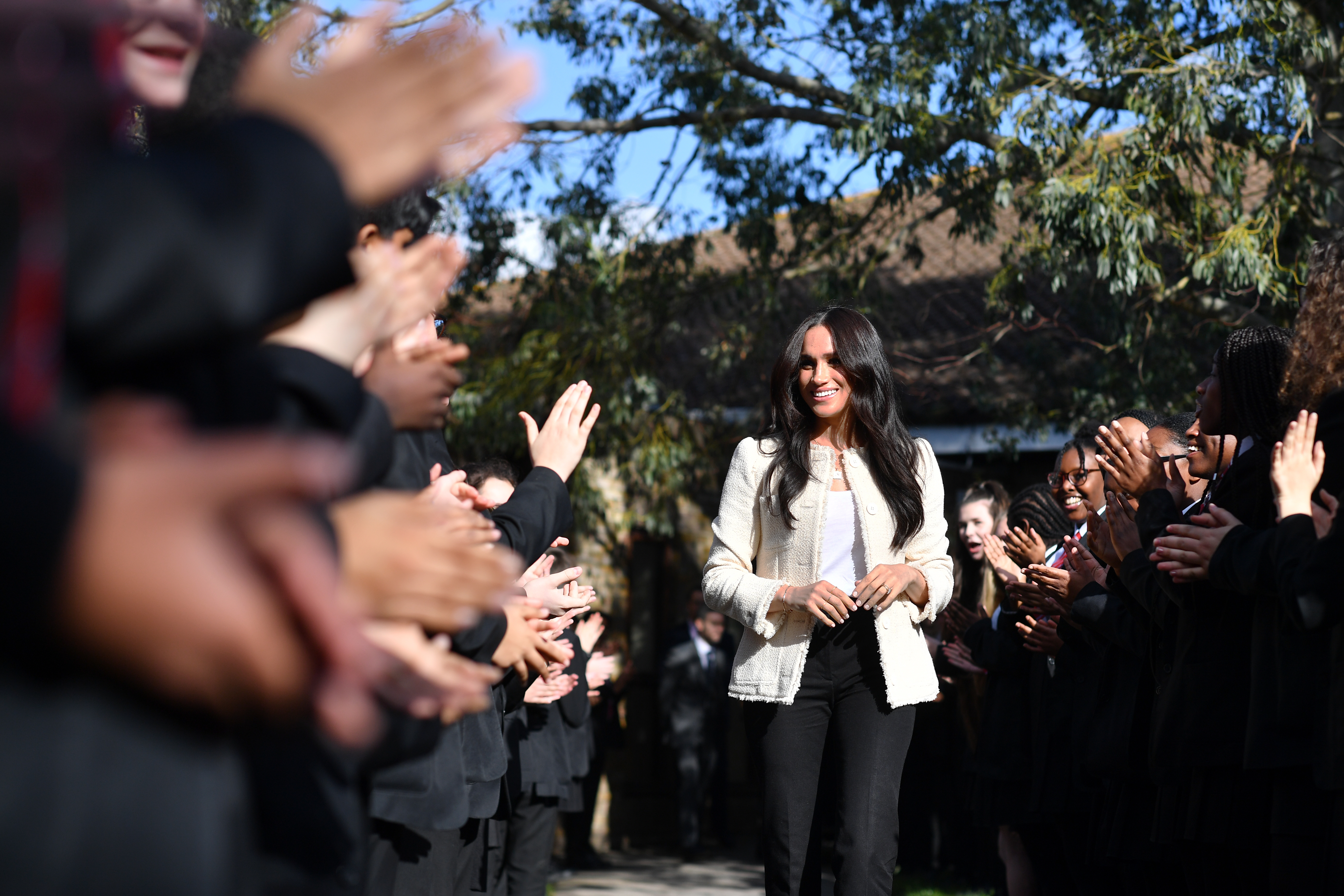 The Duchess of Sussex is greeted by pupils at the Robert Clack Upper School in Dagenham, Essex, during a surprise visit to celebrate International Women's Day.