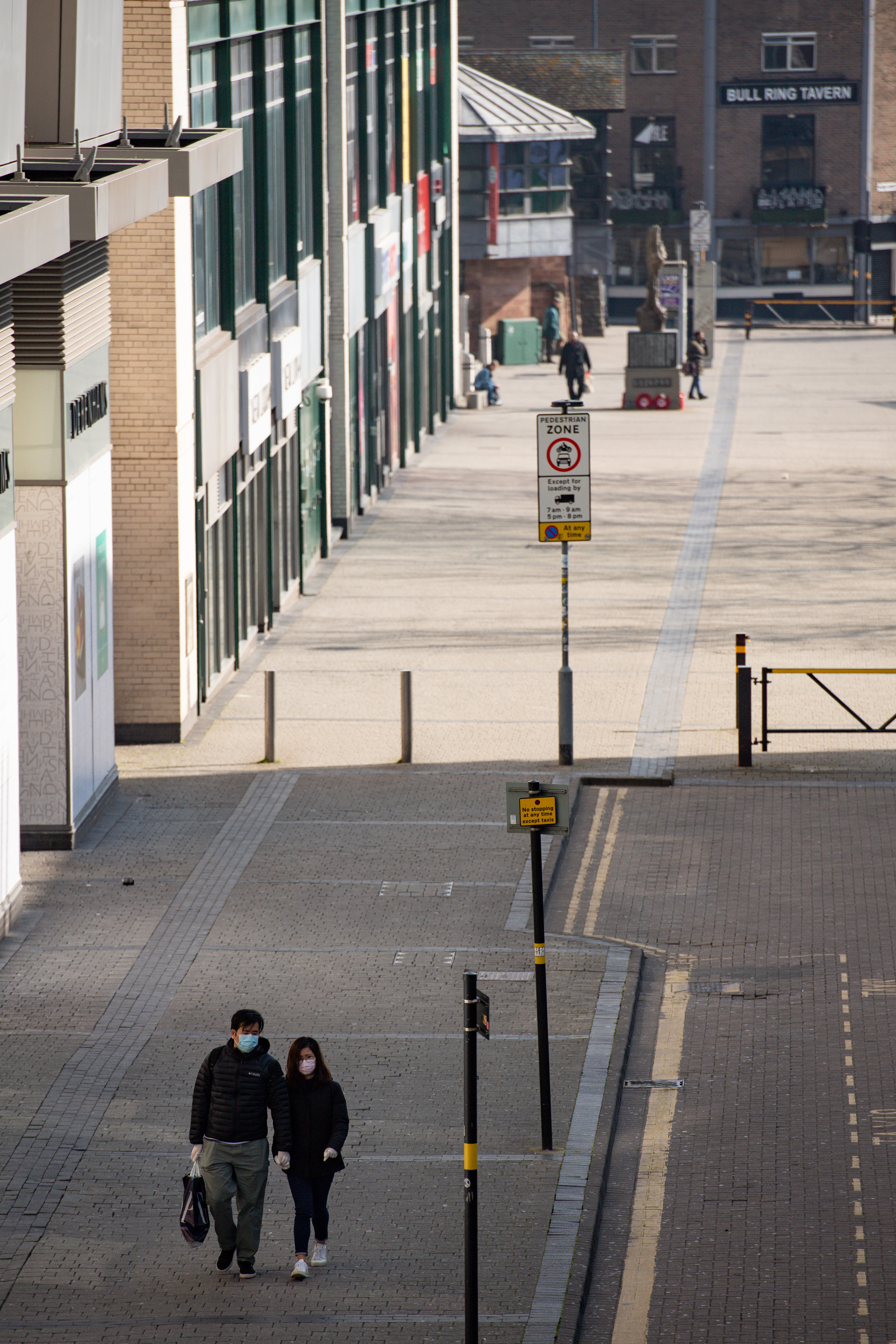 A couple wearing protevtive equipment walk by the Bullring in Birmingham, the day after Prime Minister Boris Johnson put the UK in lockdown to help curb the spread of the coronavirus.