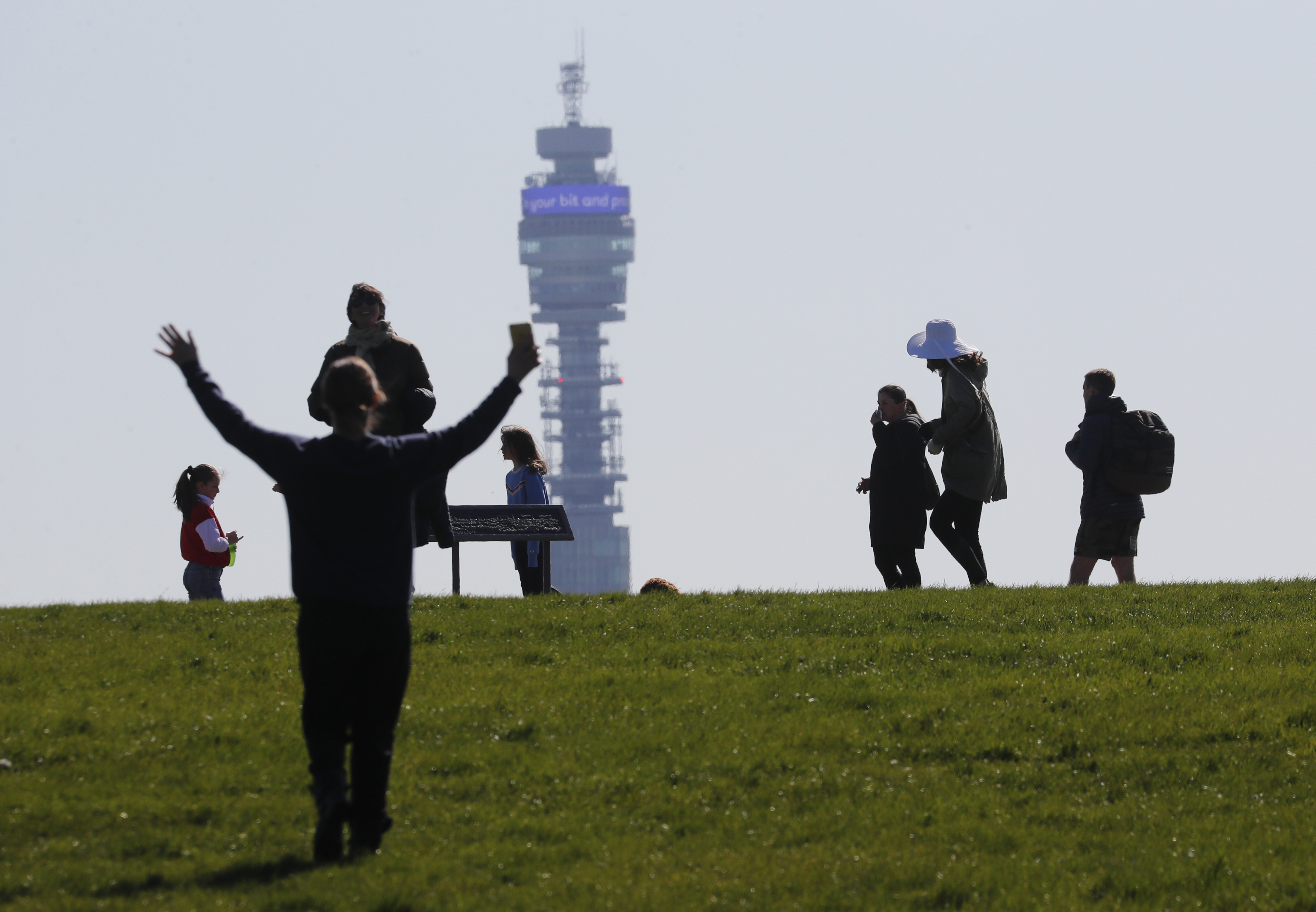 Pedestrians walk on Primrose Hill with the Post Office Tower as a backdrop in London, Monday, March 23, 2020. The British government is encouraging people to practice social distancing to help prohibit the spread of Coronavirus, further restrictions may be imposed if the public do not adhere to their advice. For most people, the new coronavirus causes only mild or moderate symptoms, such as fever and cough. For some, especially older adults and people with existing health problems, it can cause more severe illness, including pneumonia. (AP Photo/Frank Augstein)