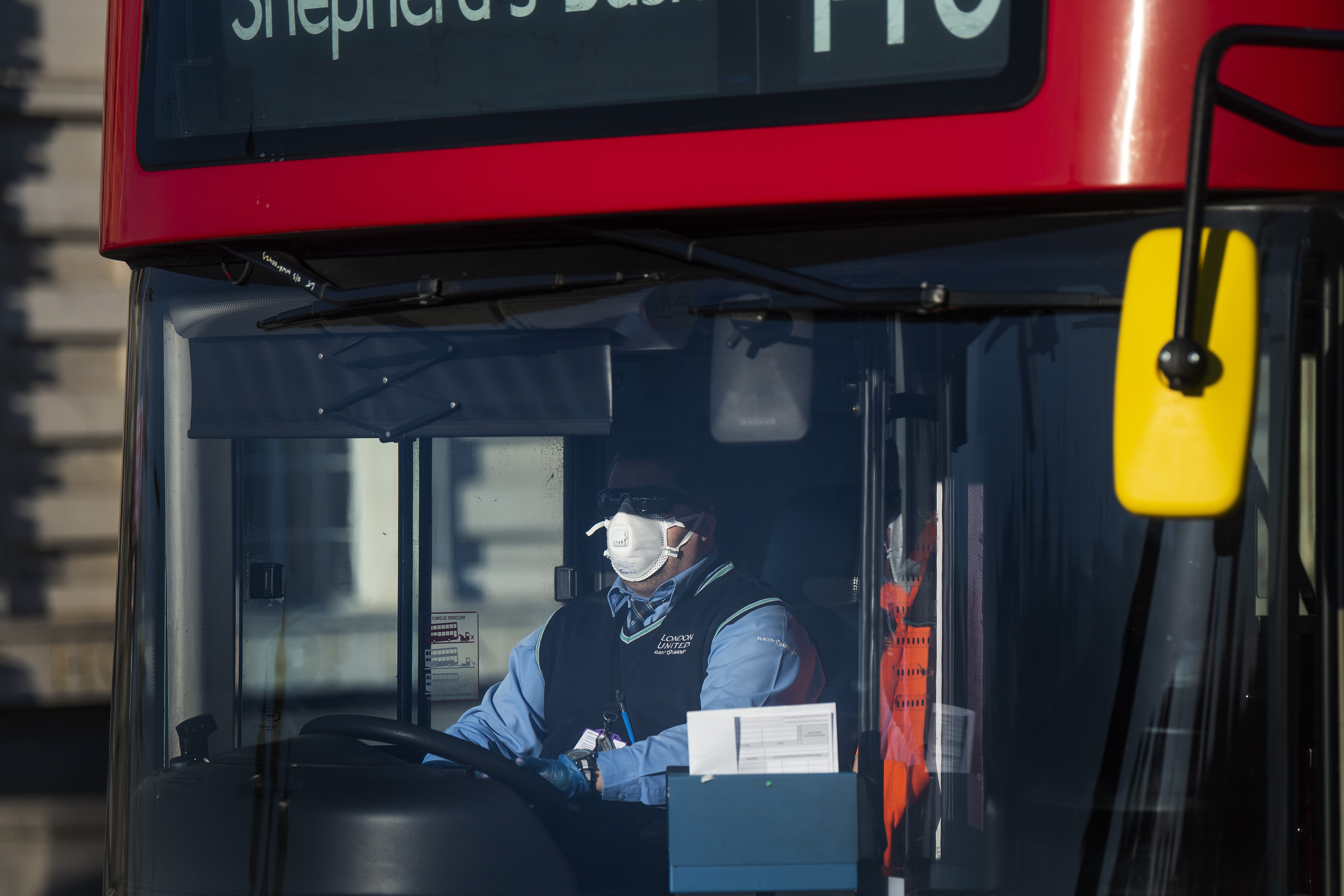 A London bus driver wearing a protective face mask on Westminster Bridge, London, after Prime Minister Boris Johnson made the decision to put the UK in lockdown to help curb the spread of the coronavirus.