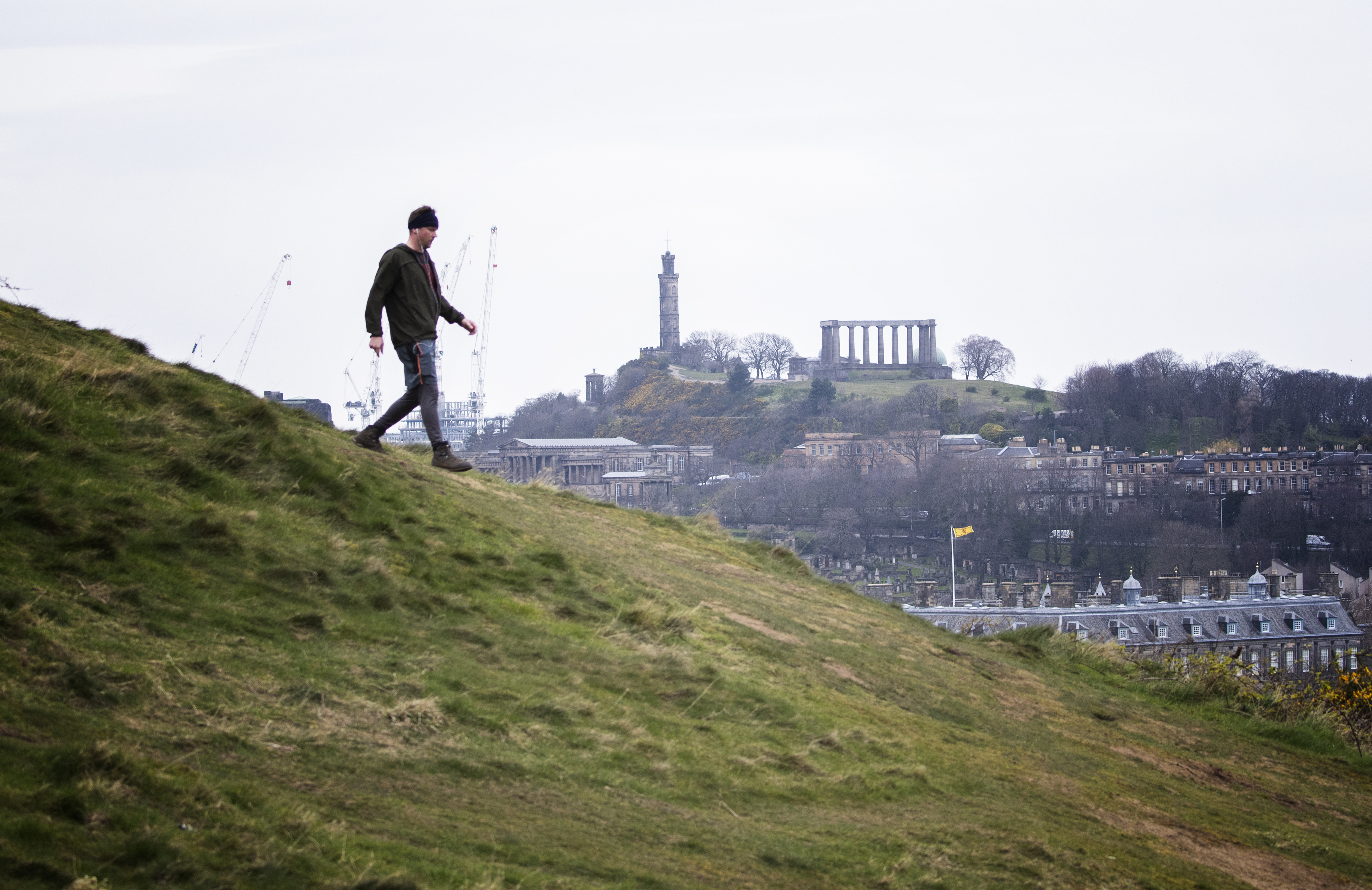 A man walks in Holyrood Park, Edinburgh, the day after Prime Minister Boris Johnson put the UK in lockdown to help curb the spread of the coronavirus.