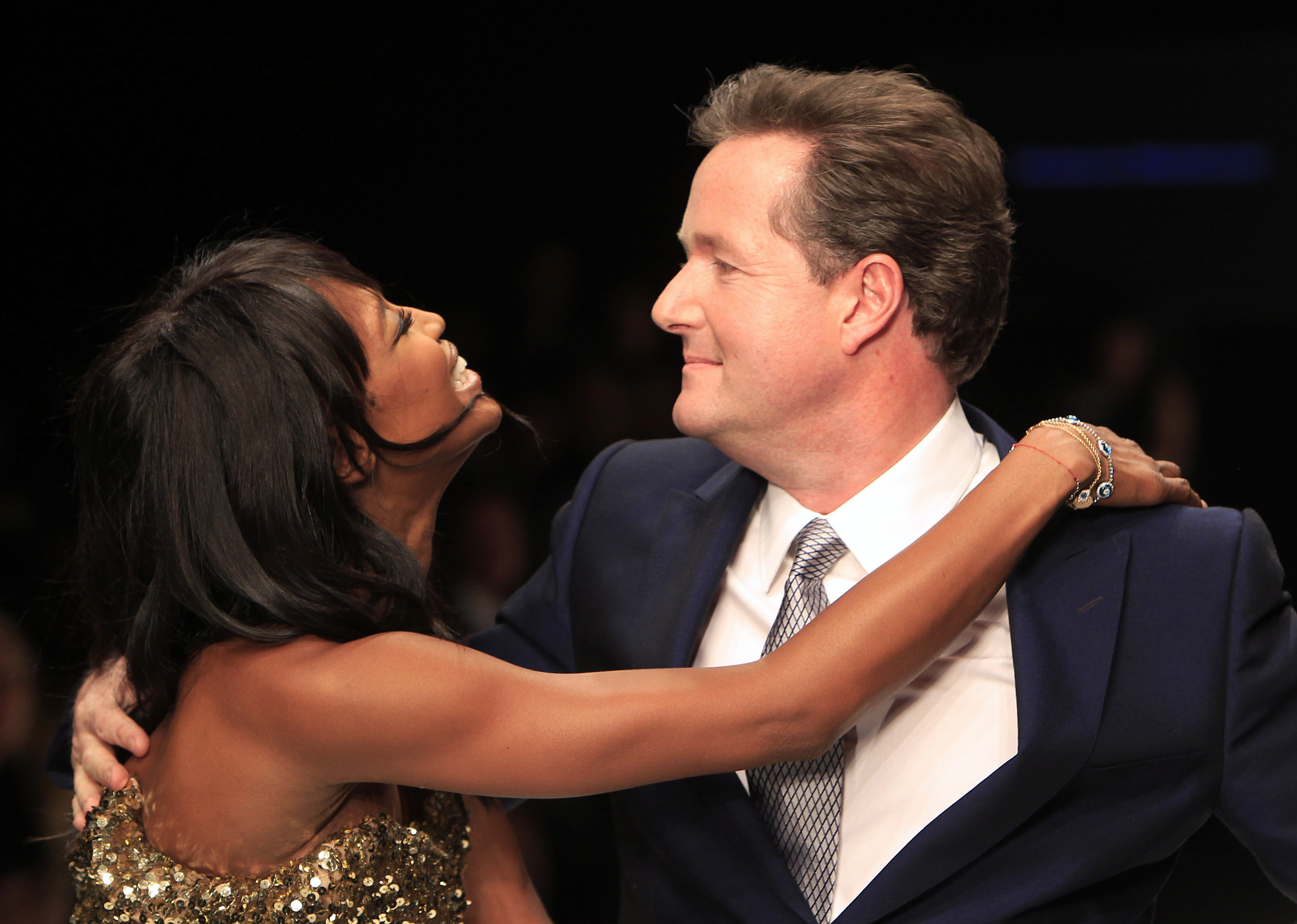 Model Naomi Campbell (L) walks down the catwalk with British television personality Piers Morgan during the Fashion For Relief Haiti fashion show and auction in London, February 18, 2010. REUTERS/Suzanne Plunkett (BRITAIN - Tags: FASHION)