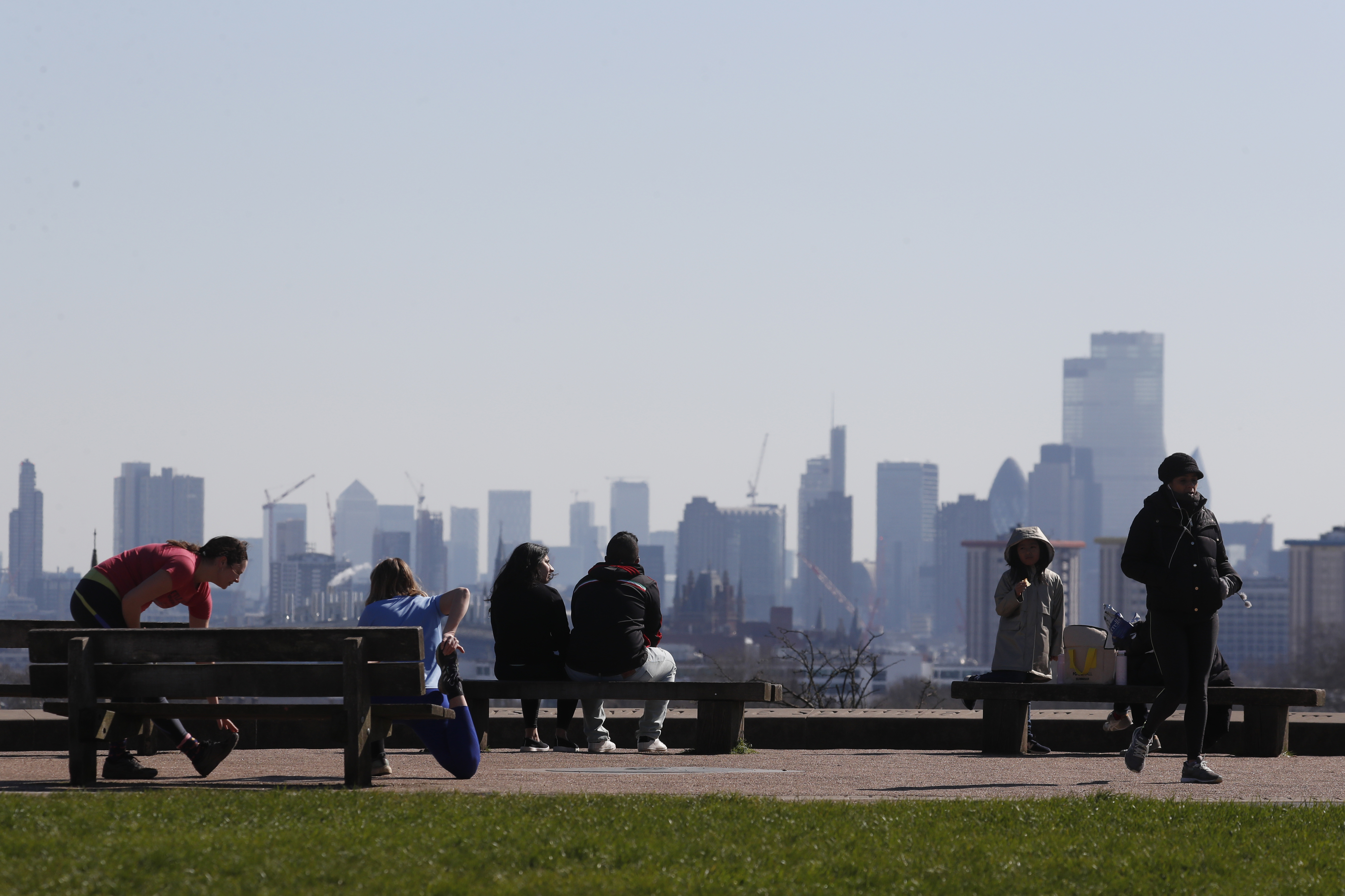 Pedestrians walk on Primrose Hill with the skyline of central London as a backdrop in London, Monday, March 23, 2020. The British government is encouraging people to practice social distancing to help prohibit the spread of Coronavirus, further restrictions may be imposed if the public do not adhere to their advice. For most people, the new coronavirus causes only mild or moderate symptoms, such as fever and cough. For some, especially older adults and people with existing health problems, it can cause more severe illness, including pneumonia. (AP Photo/Frank Augstein)