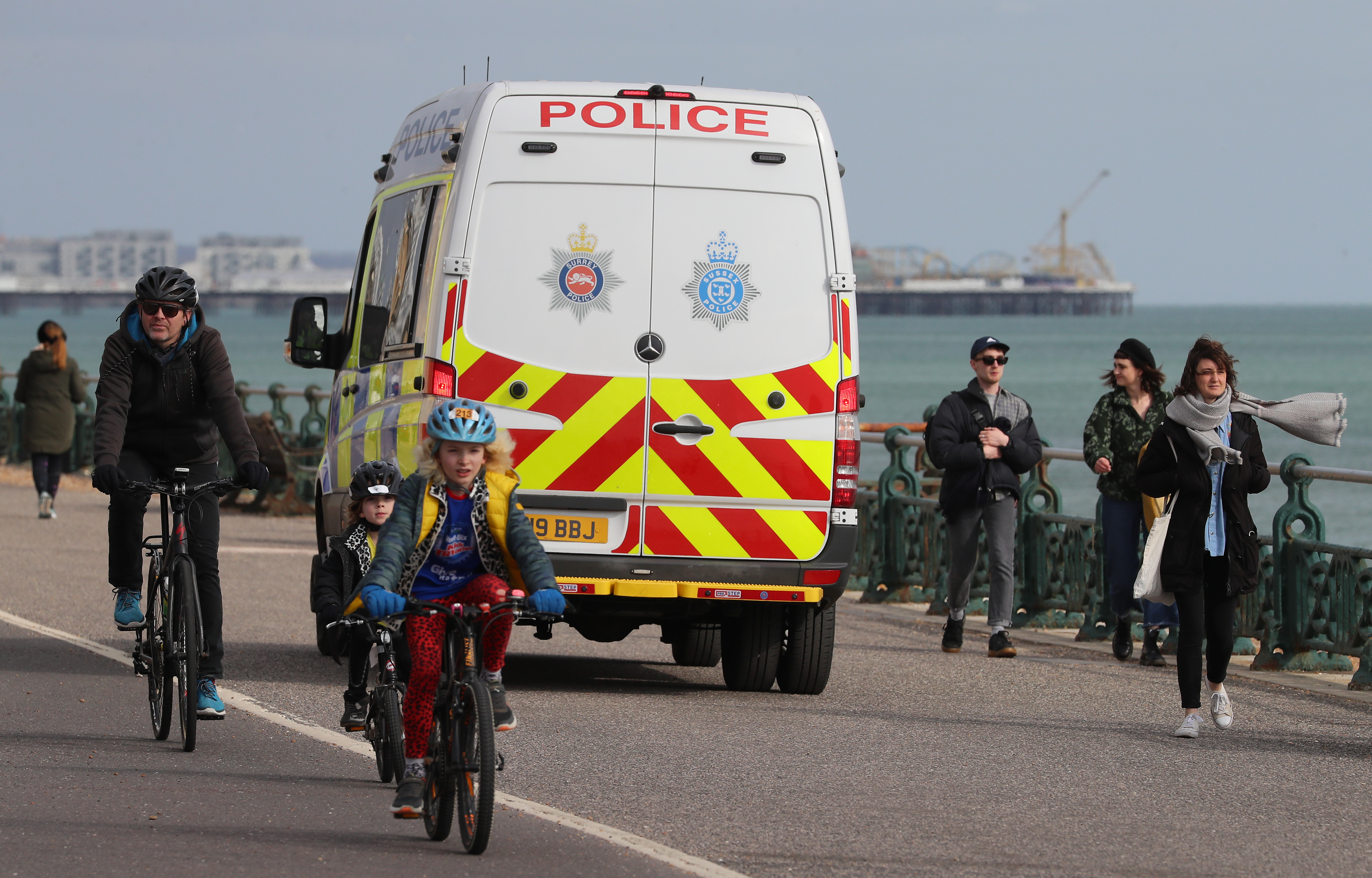 A Sussex Police van moves amongst people walking along the promenade in Brighton as the UK continues in lockdown to help curb the spread of the coronavirus.