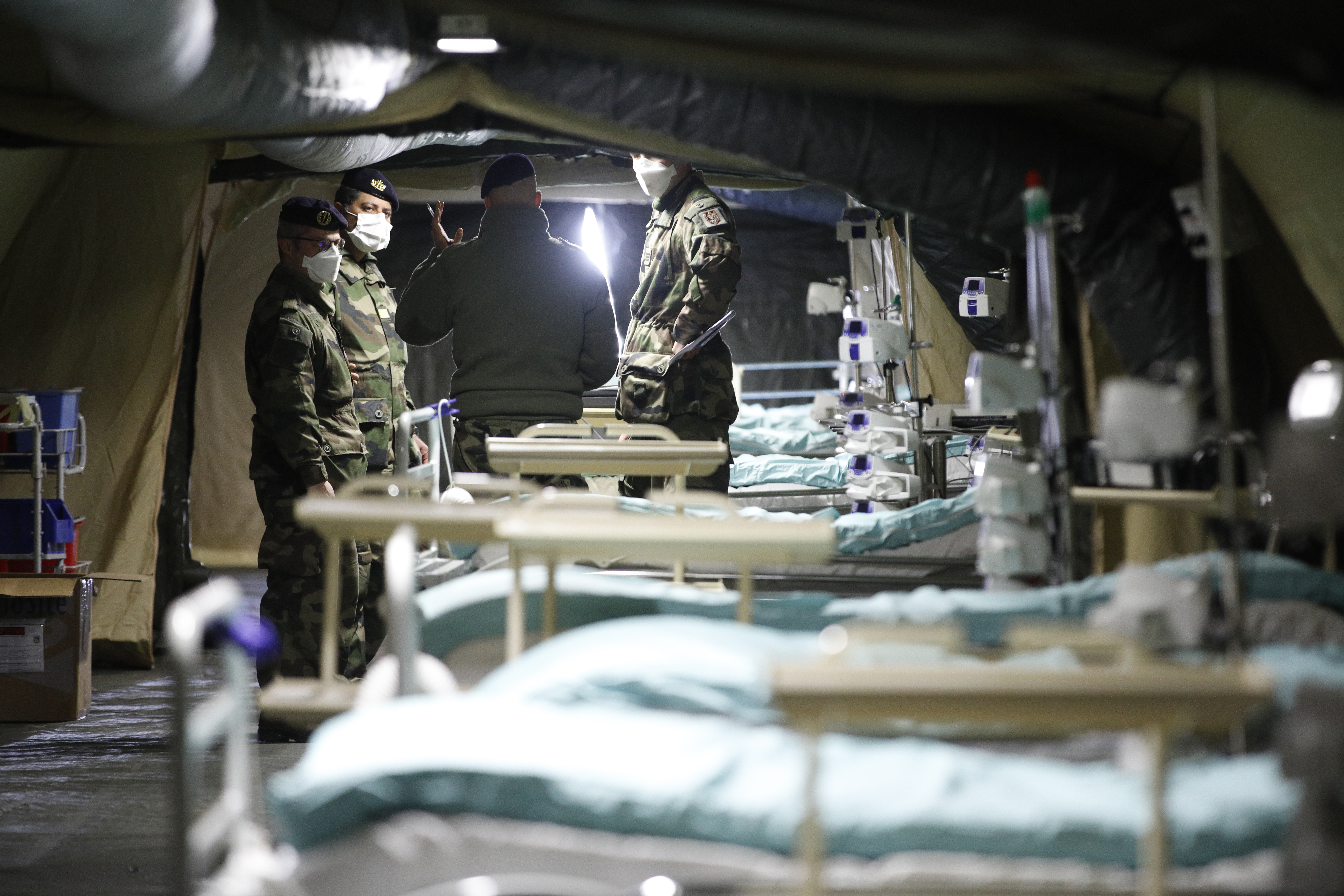 French soldiers discuss inside the military field hospital built in Mulhouse, eastern France, Monday March 23, 2020. The Grand Est region is now the epicenter of the outbreak in France, which has buried the third most virus victims in Europe, after Italy and Spain. For most people, the new coronavirus causes only mild or moderate symptoms. For some it can cause more severe illness. (AP Photo/Jean-Francois Badias)