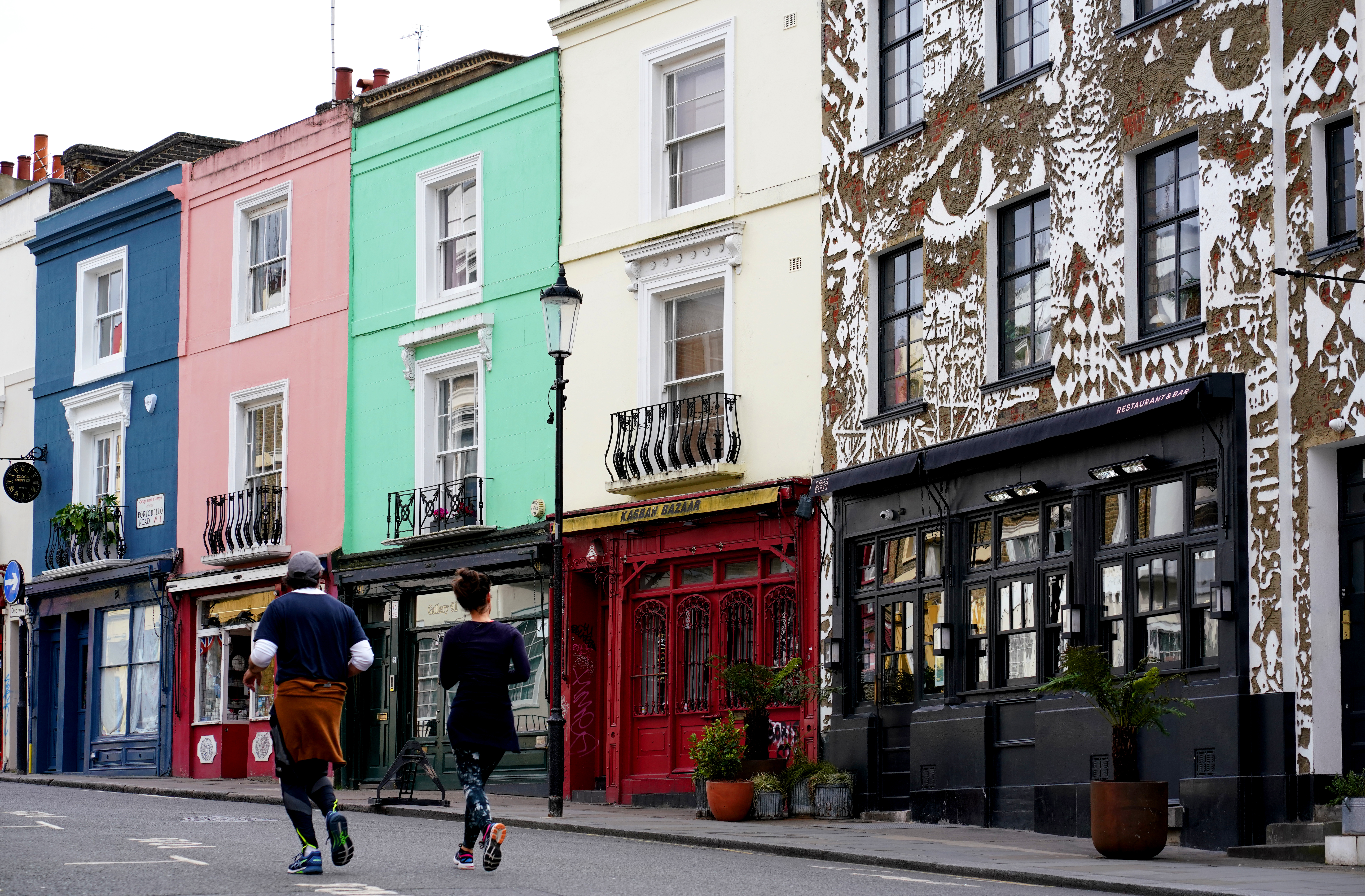 Members of the public jog down Portobello Road in Notting Hill, London as the UK continues in lockdown to help curb the spread of the coronavirus.