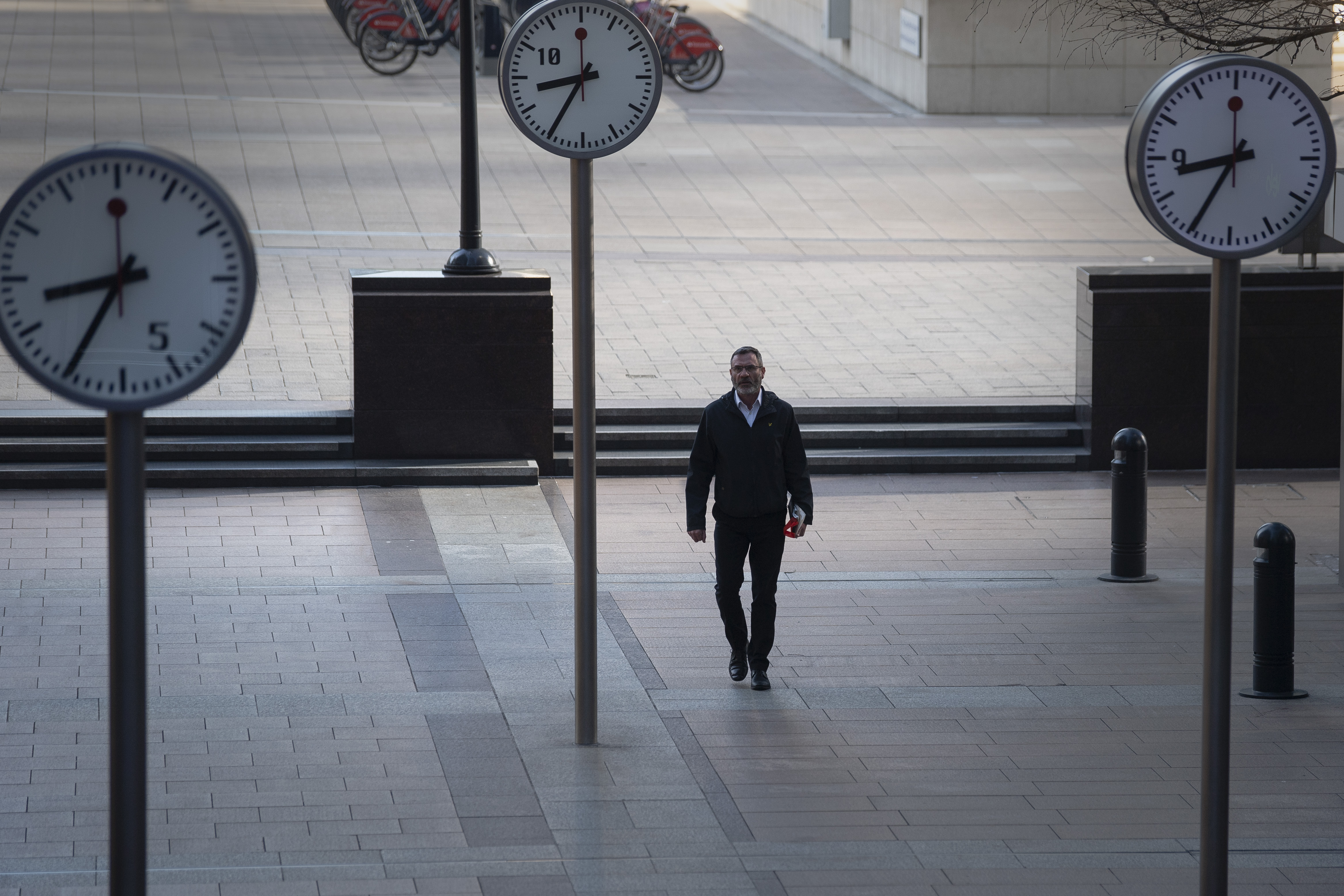 A man walks in Canary Wharf, London during rush hour, after Prime Minister Boris Johnson has put the UK in lockdown to help curb the spread of the coronavirus.