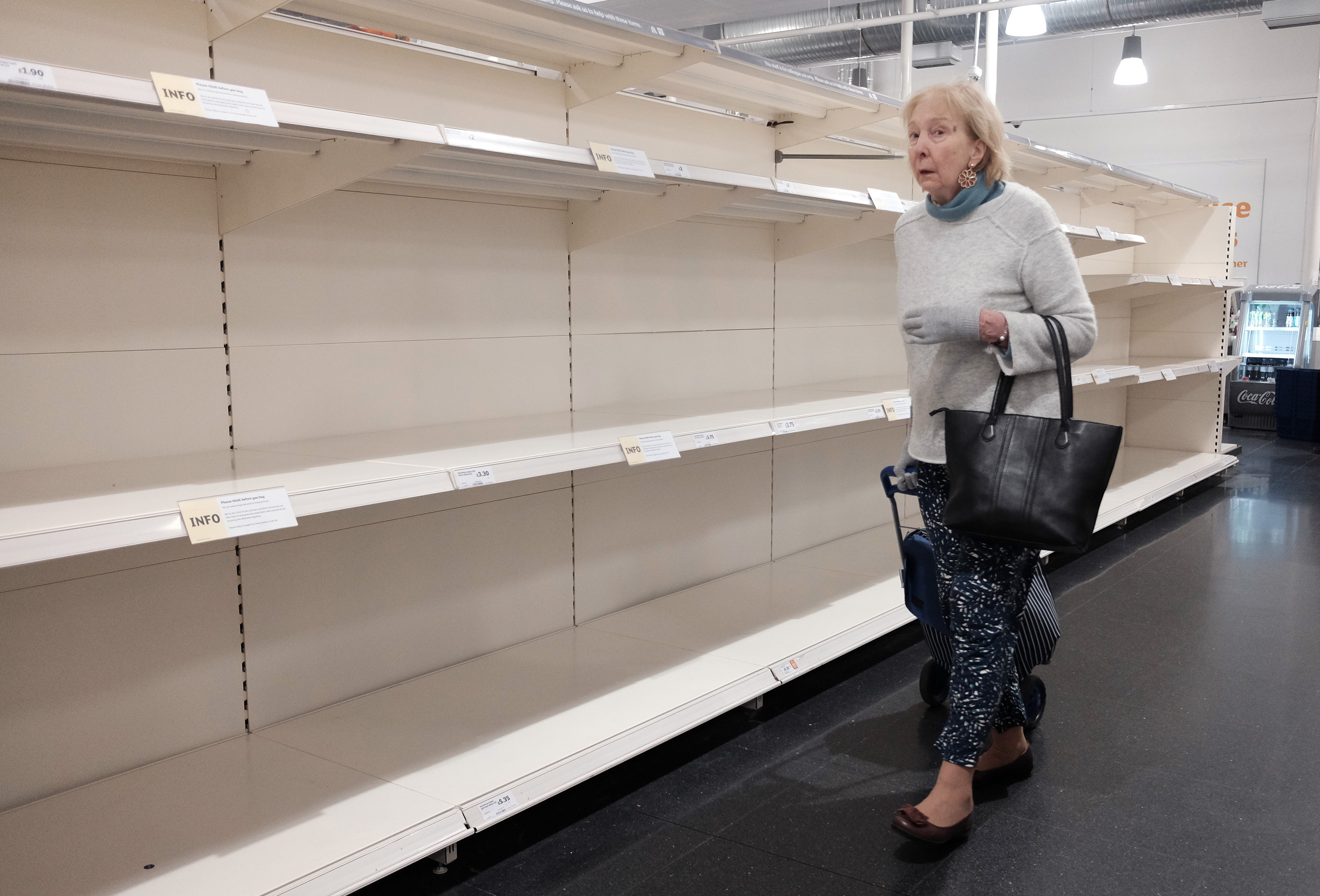 A lady looking at empty shelves in a Sainsbury's store in London, as the death toll from coronavirus in the UK reached 71 people.