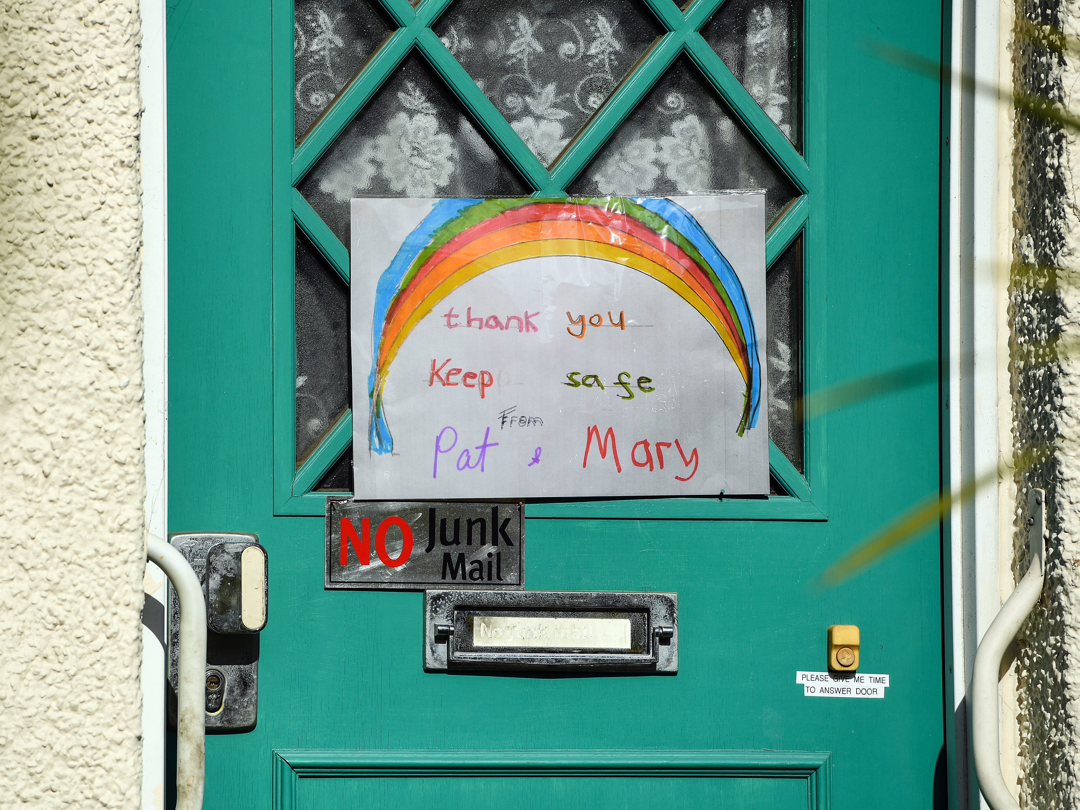 Hand painted pictures of colourful rainbows are displayed on the door of a home in South London as the UK continues in lockdown to help curb the spread of the coronavirus.