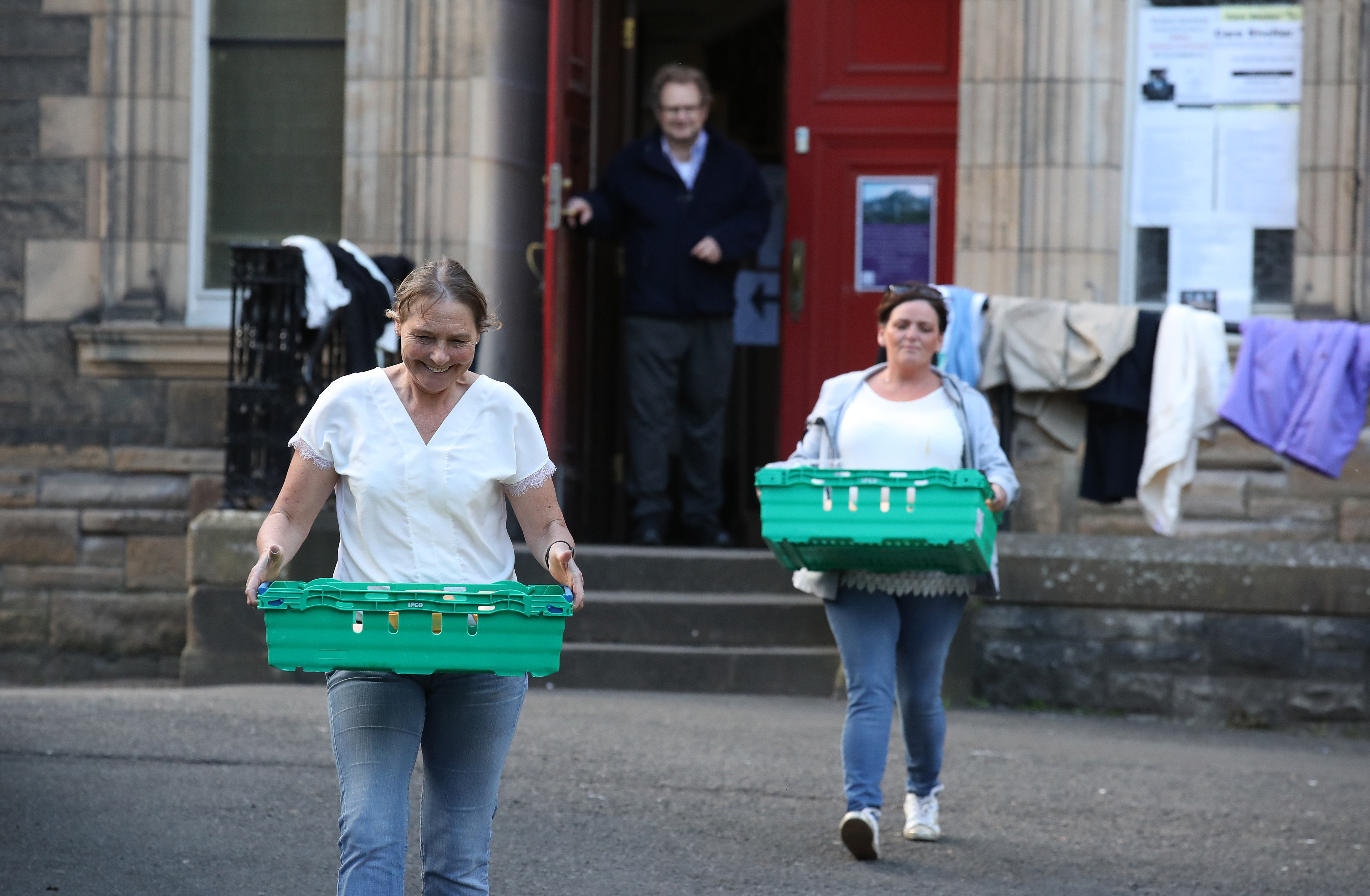 Volunteers from the Step to Hope charity carry meals to give to those who want one in the grounds of The Parish Church of St Cuthbert in Edinburgh. The charity in Edinburgh which is handing out meals to the homeless, normally meals are served inside the church, however due to restrictions these are being handed outside to the homeless as the UK continues in lockdown to help curb the spread of the coronavirus.