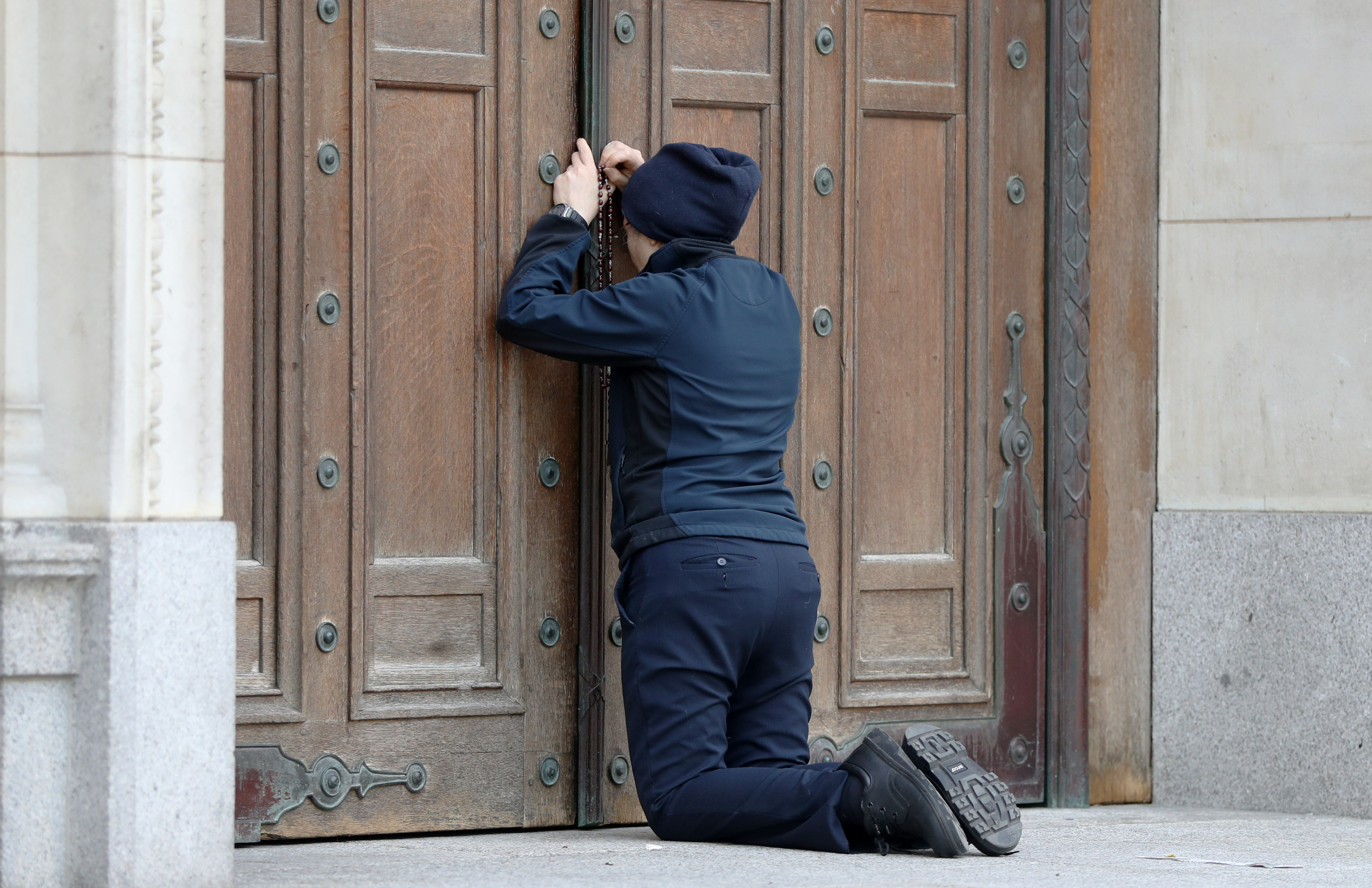 A woman prays at the closed doors of Westminster Cathedral ahead of the Easter morning mass, London, as the UK continues in lockdown to help curb the spread of the coronavirus. Churches across the country have been continuing to broadcast services digitally in the lead-up to Easter, with more than 1,000 livestreams taking place on a regular basis.