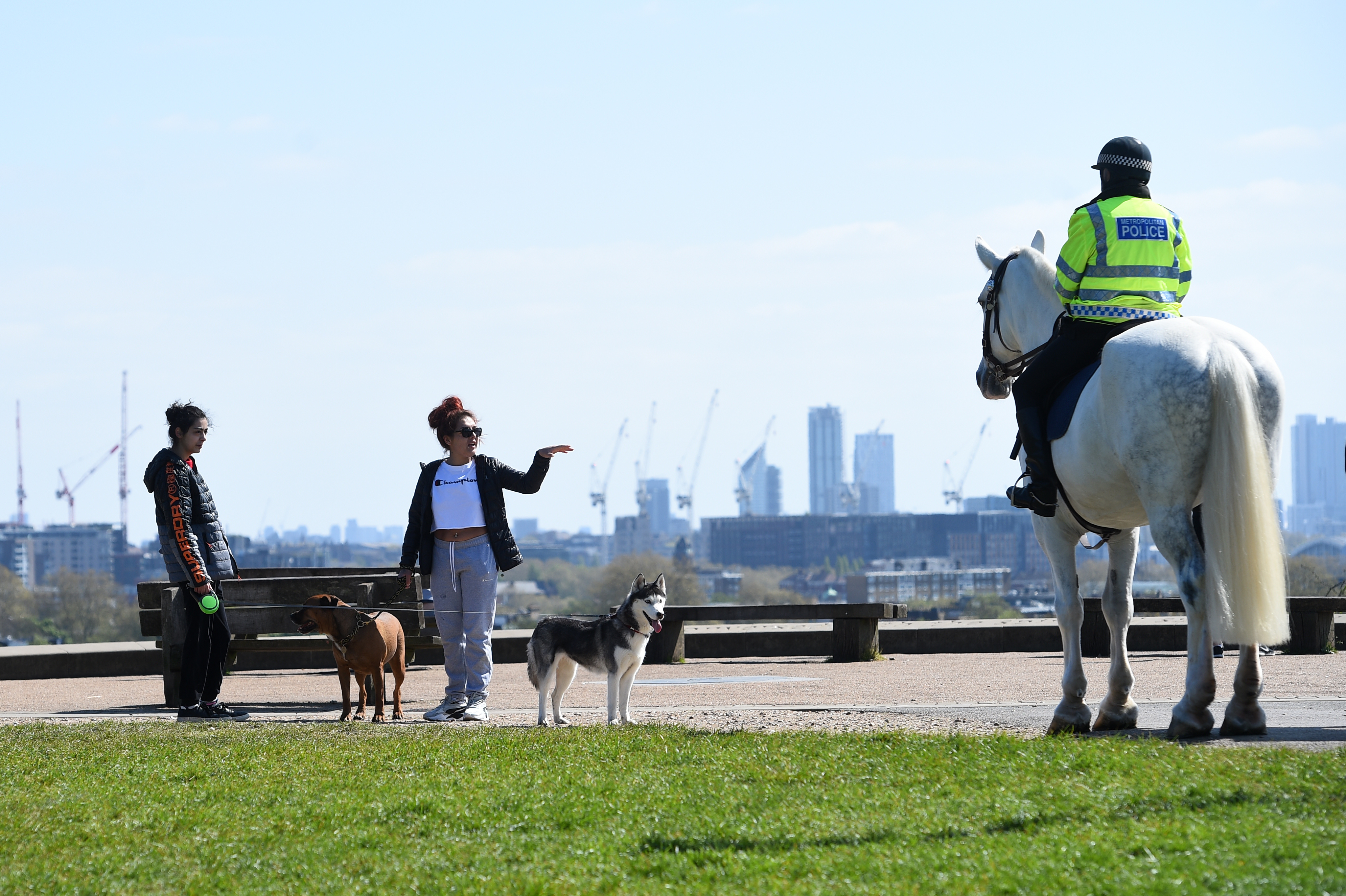 Mounted police officers speak to people on Primrose Hill, London, as the UK continues in lockdown to help curb the spread of the coronavirus.