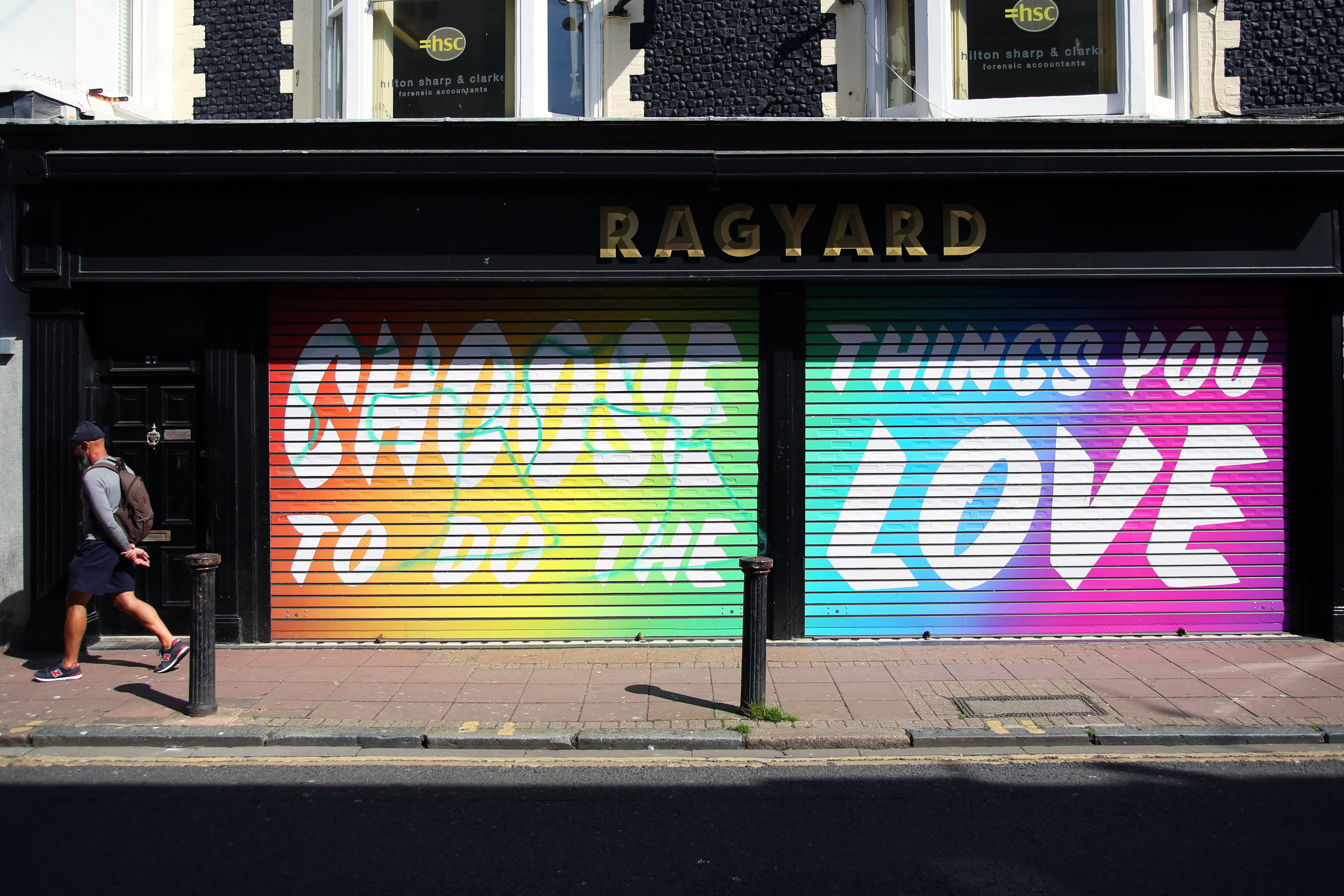 A man walks past a colourful message outside of a shop saying 'Choose to do the things you love' in Brighton as the UK continues in lockdown to help curb the spread of the coronavirus.