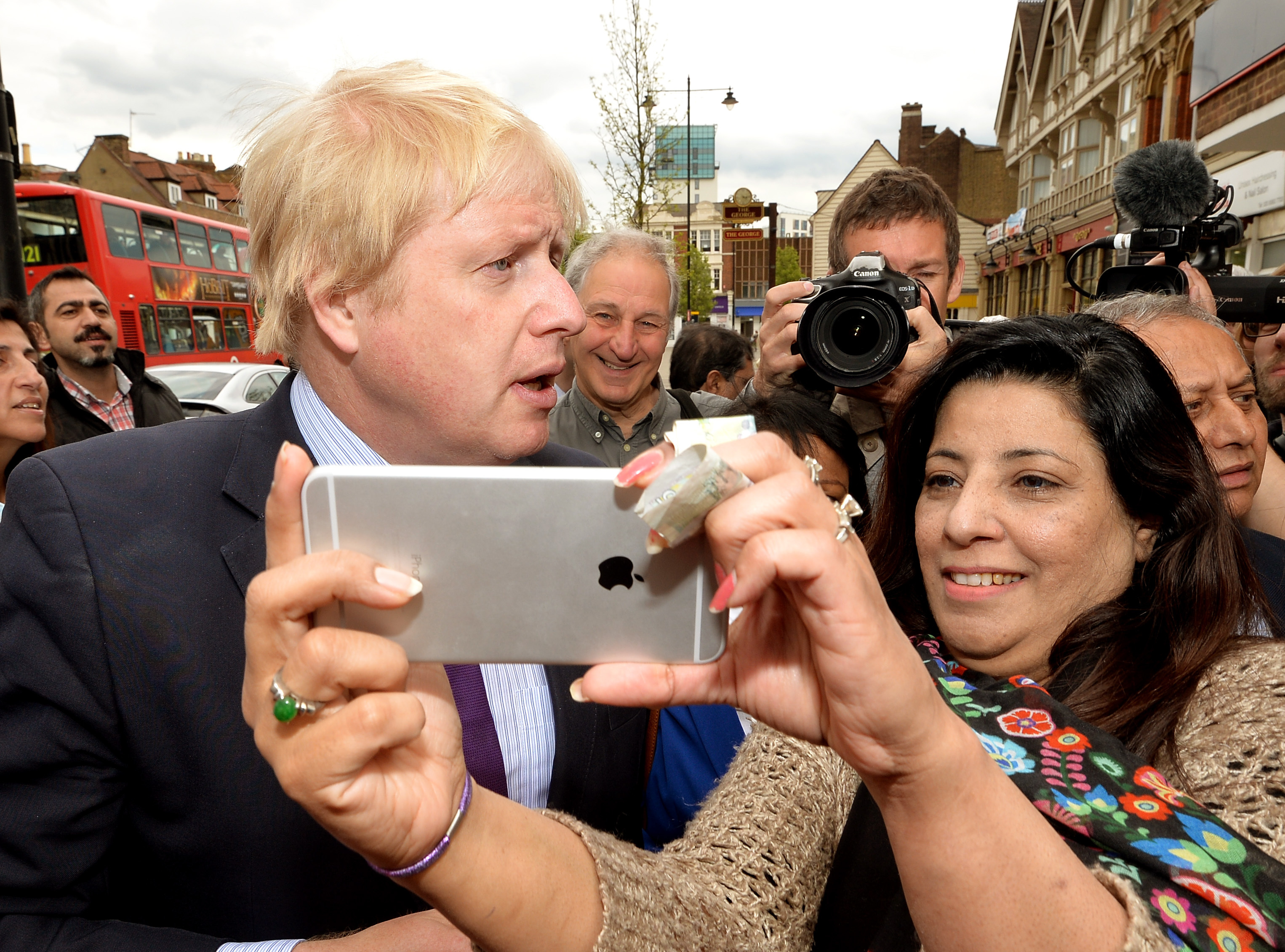 A woman takes a selfie photo with Mayor of London Boris Johnson as he speak to residents in Enfield town centre while on the General Election campaign trail, as he gives his support to local Conservative candidate Nick De Bois (not in picture).