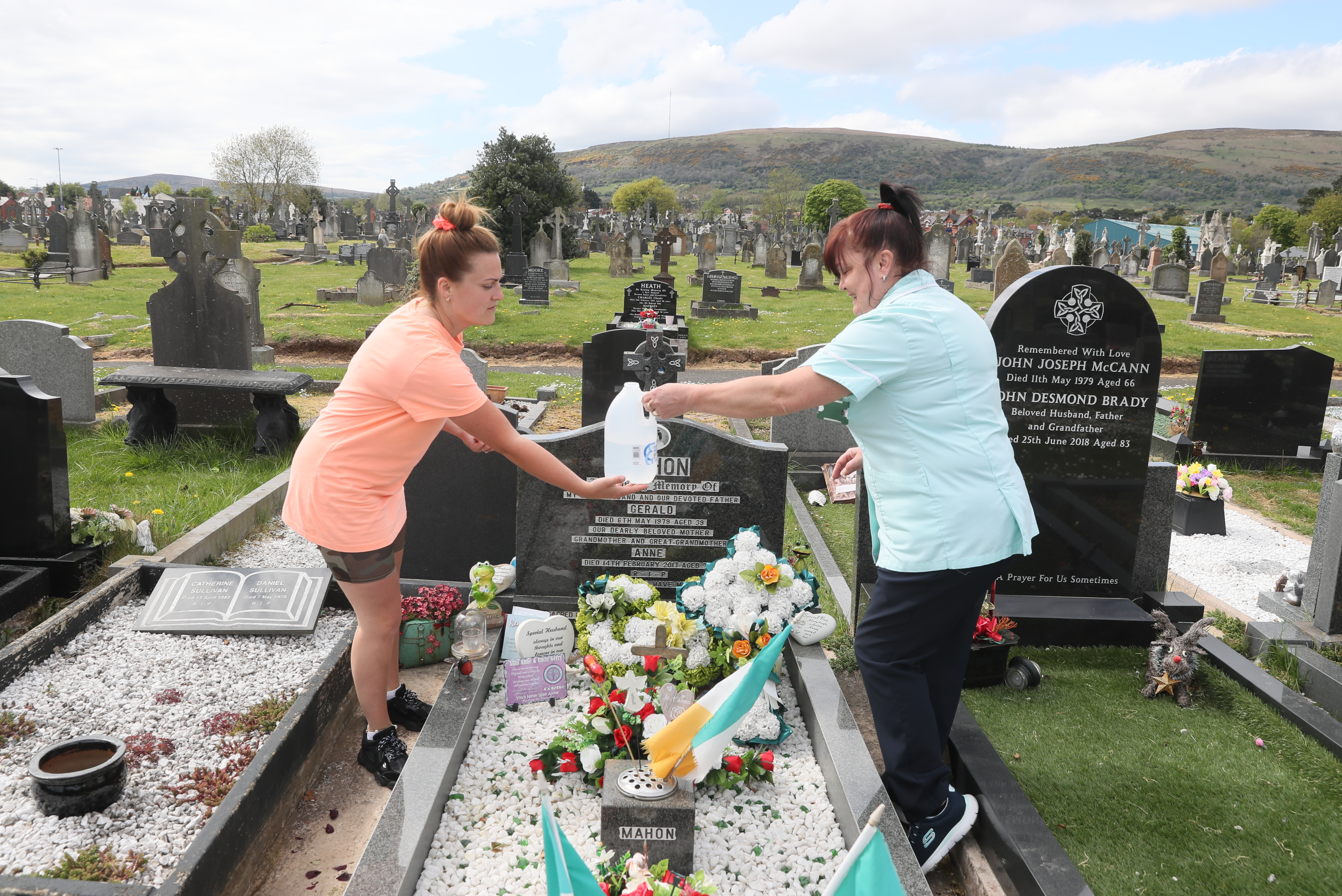 Two women water plants at Milltown Cemetery in Belfast, Northern Ireland, where cemeteries are reopening to the public this weekend, as the UK continues in lockdown to help curb the spread of the coronavirus.