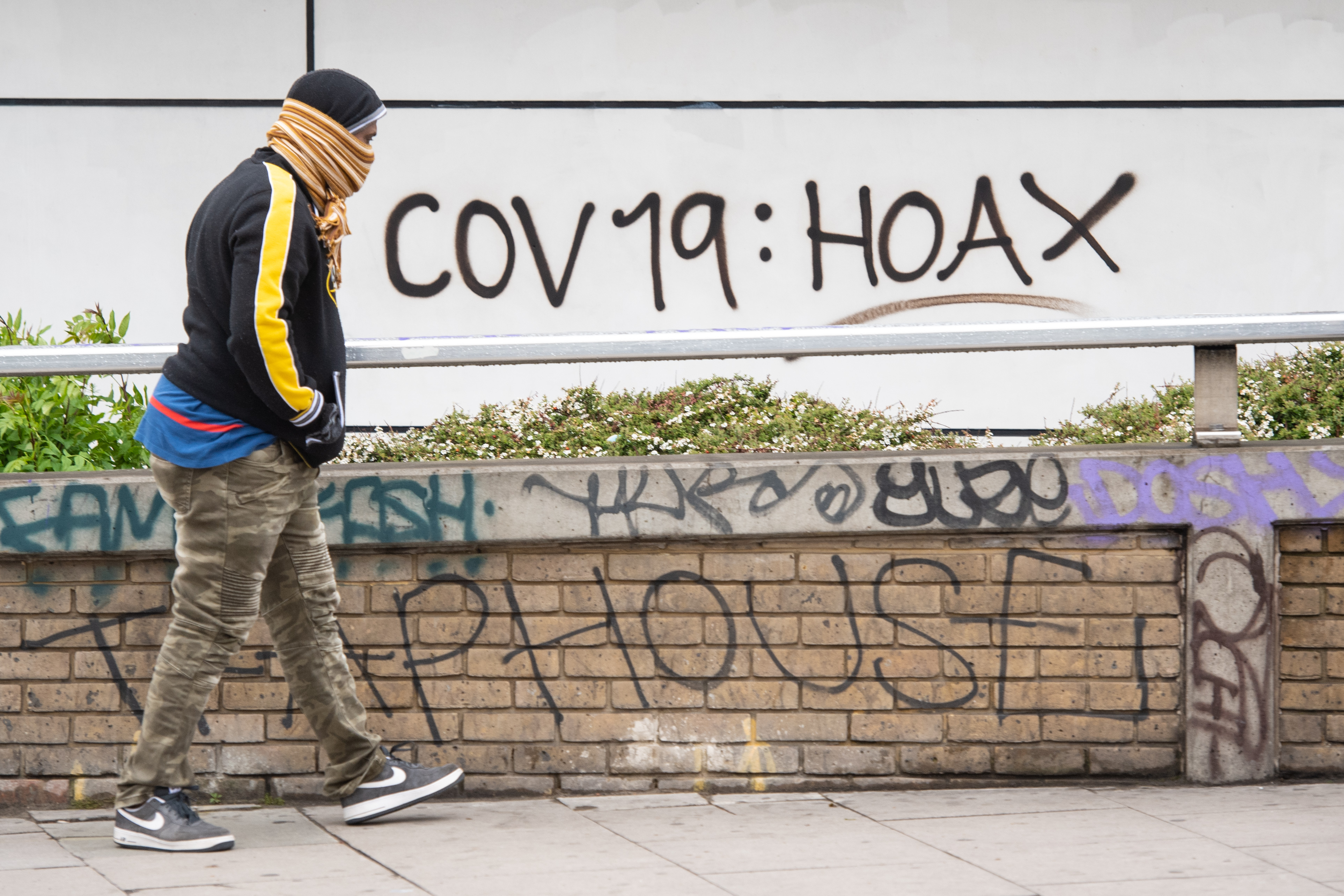 A man passes graffiti reading 'cov 19: hoax', in south London, as the UK continues in lockdown to help curb the spread of coronavirus.