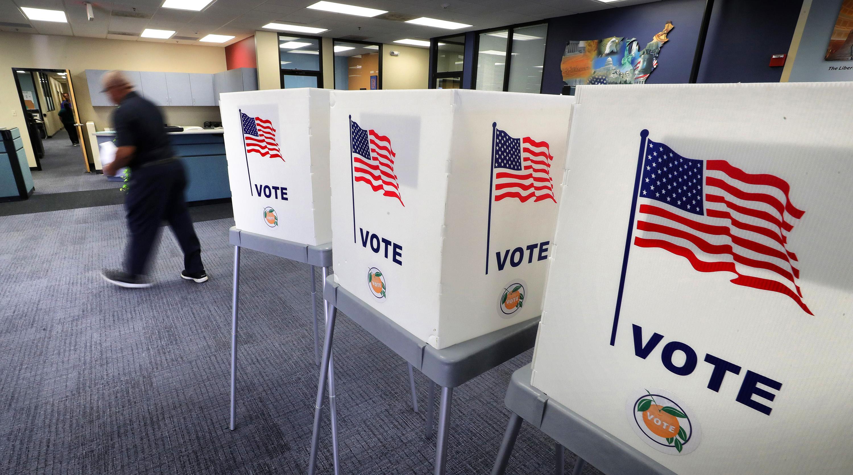 Imagem mostra cabines de votação com desenho da bandeira americana estampado na lateral, dentro de um recinto fechado.