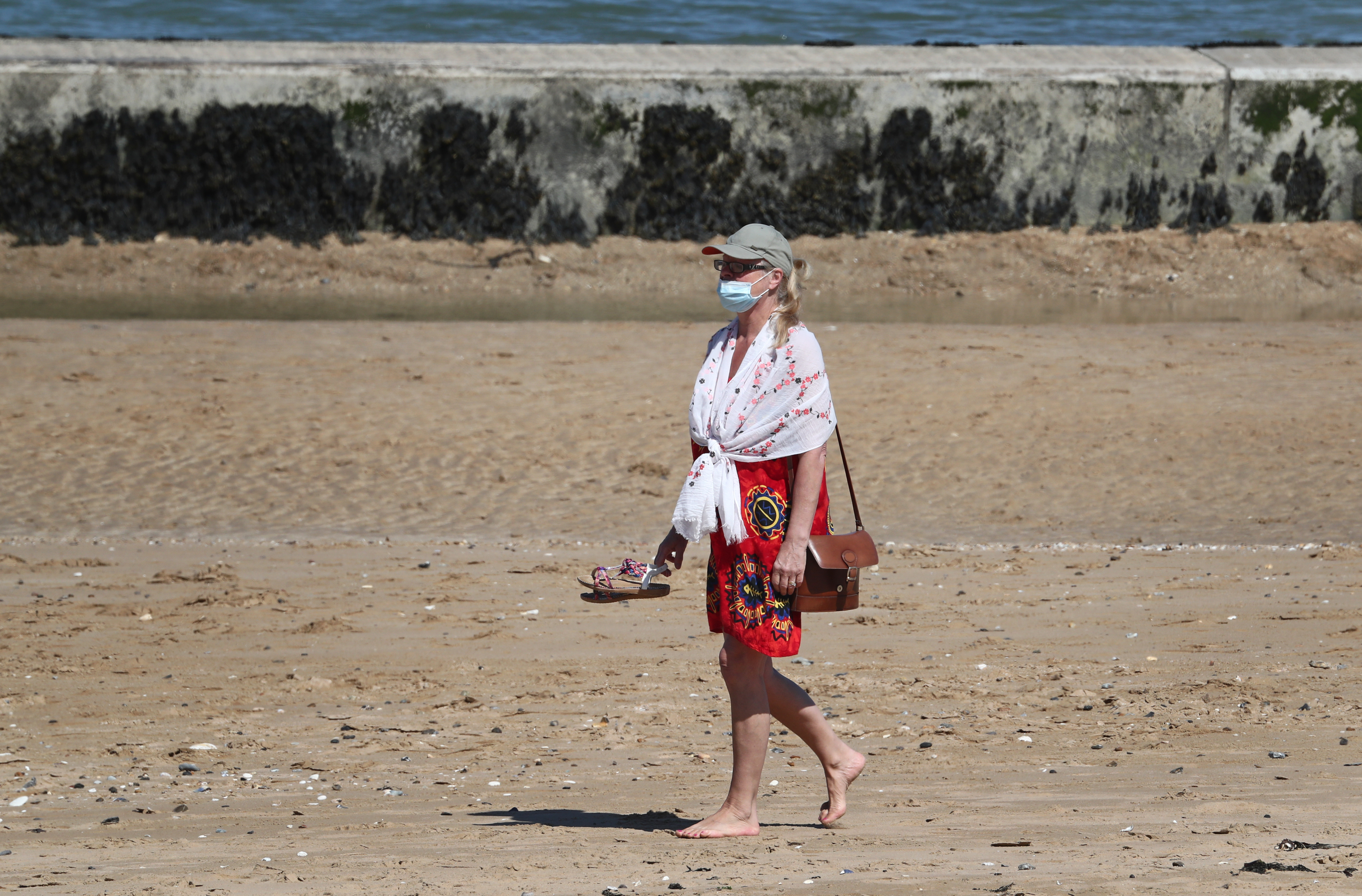 A lady in a mask walks on the beach in Margate, Kent, as the UK continues in lockdown to help curb the spread of the coronavirus.
