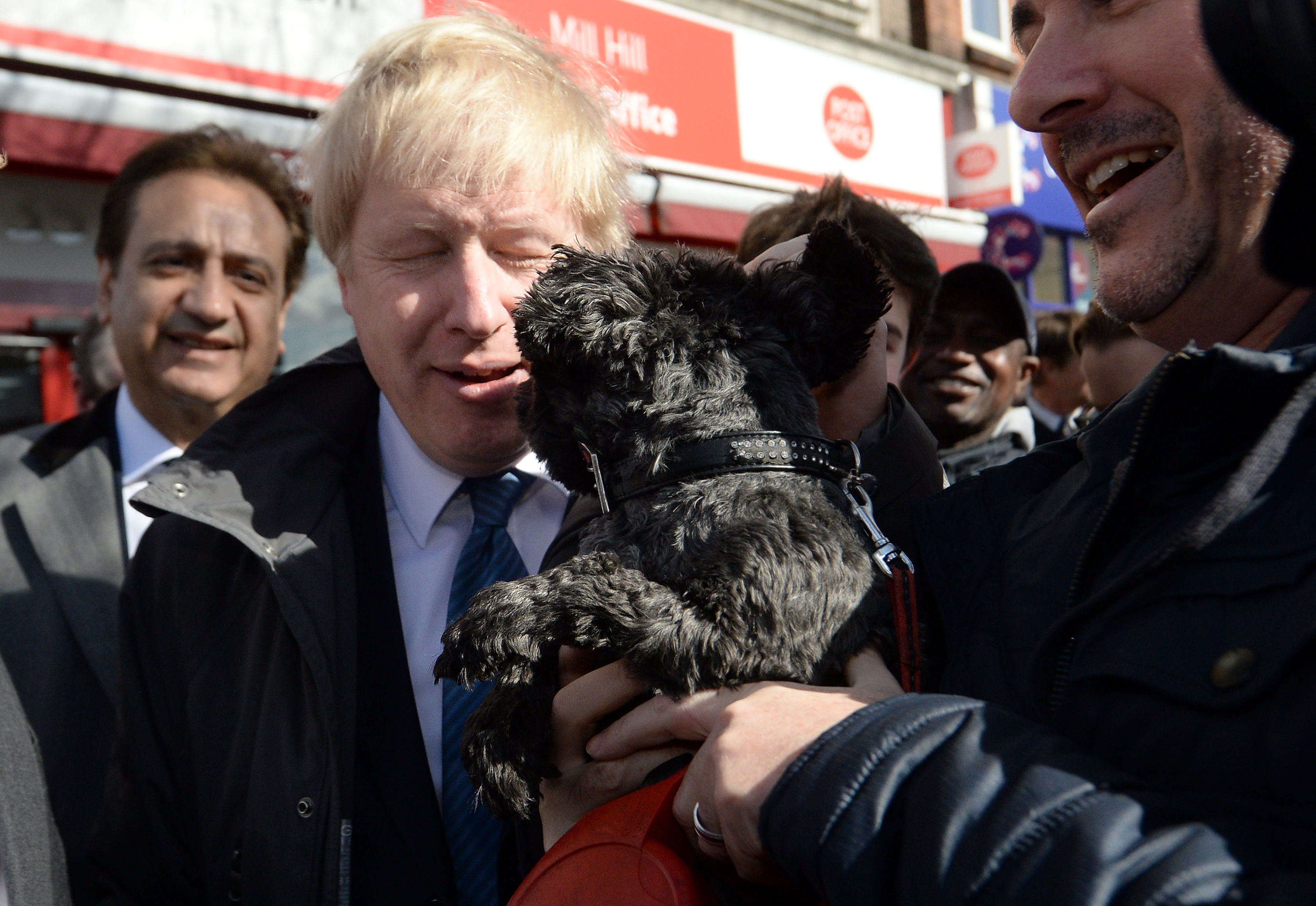 Mayor of London Boris Johnson is licked by a dog as he meets members of the public and local business owners after launching the Conservative London campaign at Hartley Hall in Mill Hill, London.