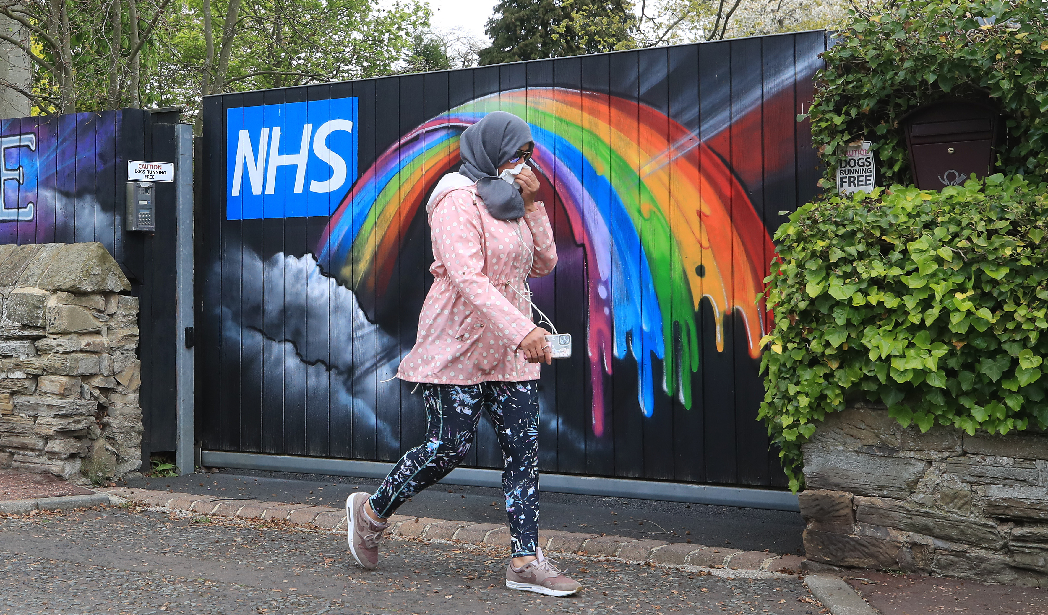 A woman walks past rainbow NHS graffiti on one of the gates to a mansion in Woolsingham in Newcastle as the UK continues in lockdown to help curb the spread of the coronavirus.
