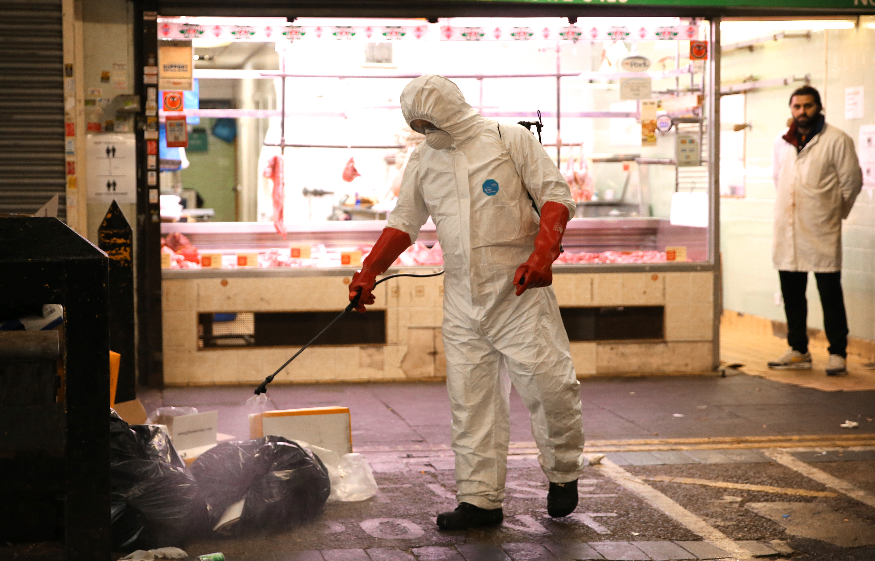 A man wearing a personal protective equipment suit uses a backpack of pressurized spray disinfectant water to remove covid-19 from the street at Queens Market in Upton Park, east London, as the UK continues in lockdown to help curb the spread of the coronavirus. Picture date: Tuesday April 28, 2020.