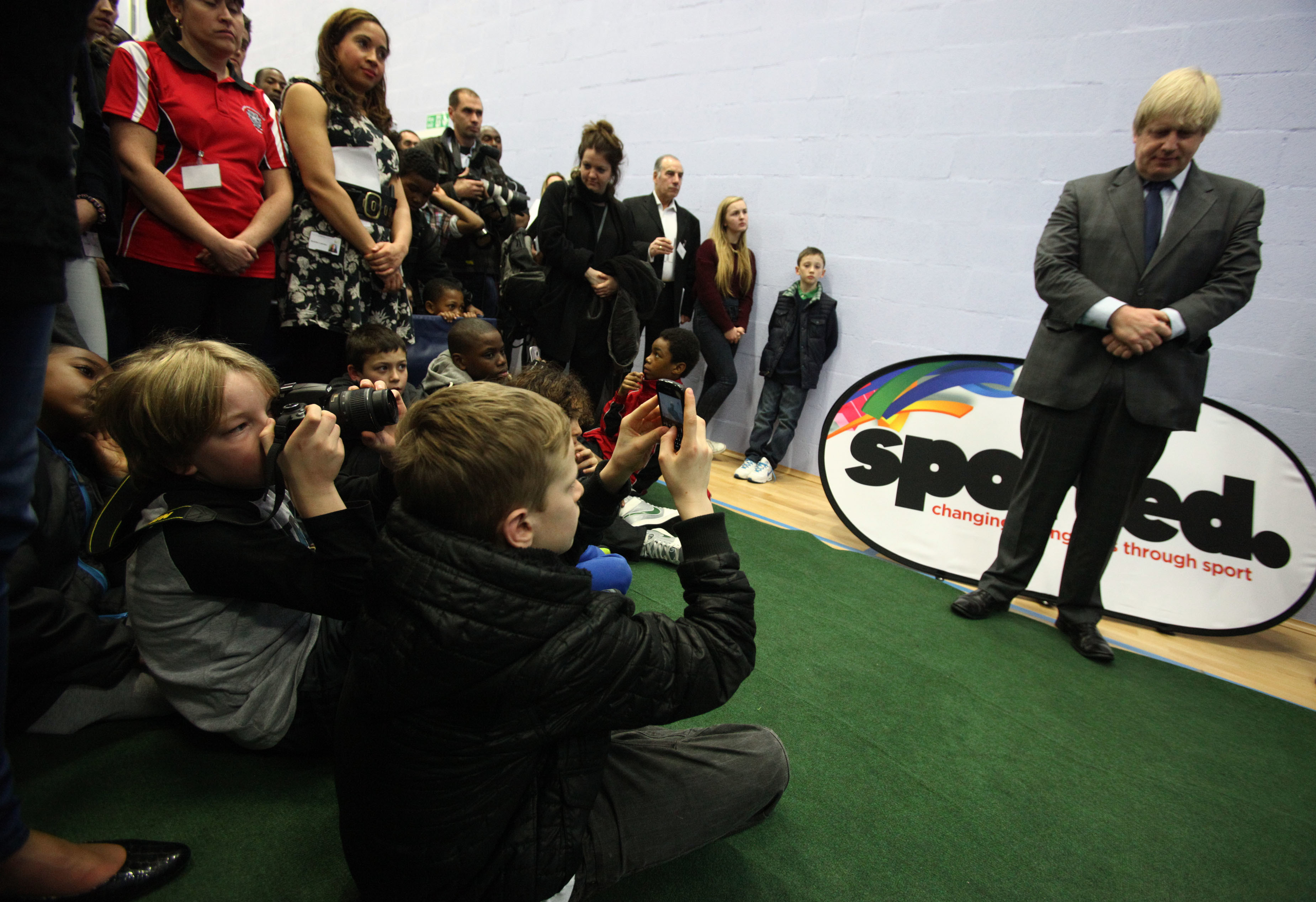 Children take pictures of Mayor of London Boris Johnson during his visit to a 100-year-old youth club that has helped 10,000 boys, at Crown and Manor Youth Club in north London. PRESS ASSOCIATION Photo. Picture date: Thursday February 28, 2013. Photo credit should read: Yui Mok/PA Wire