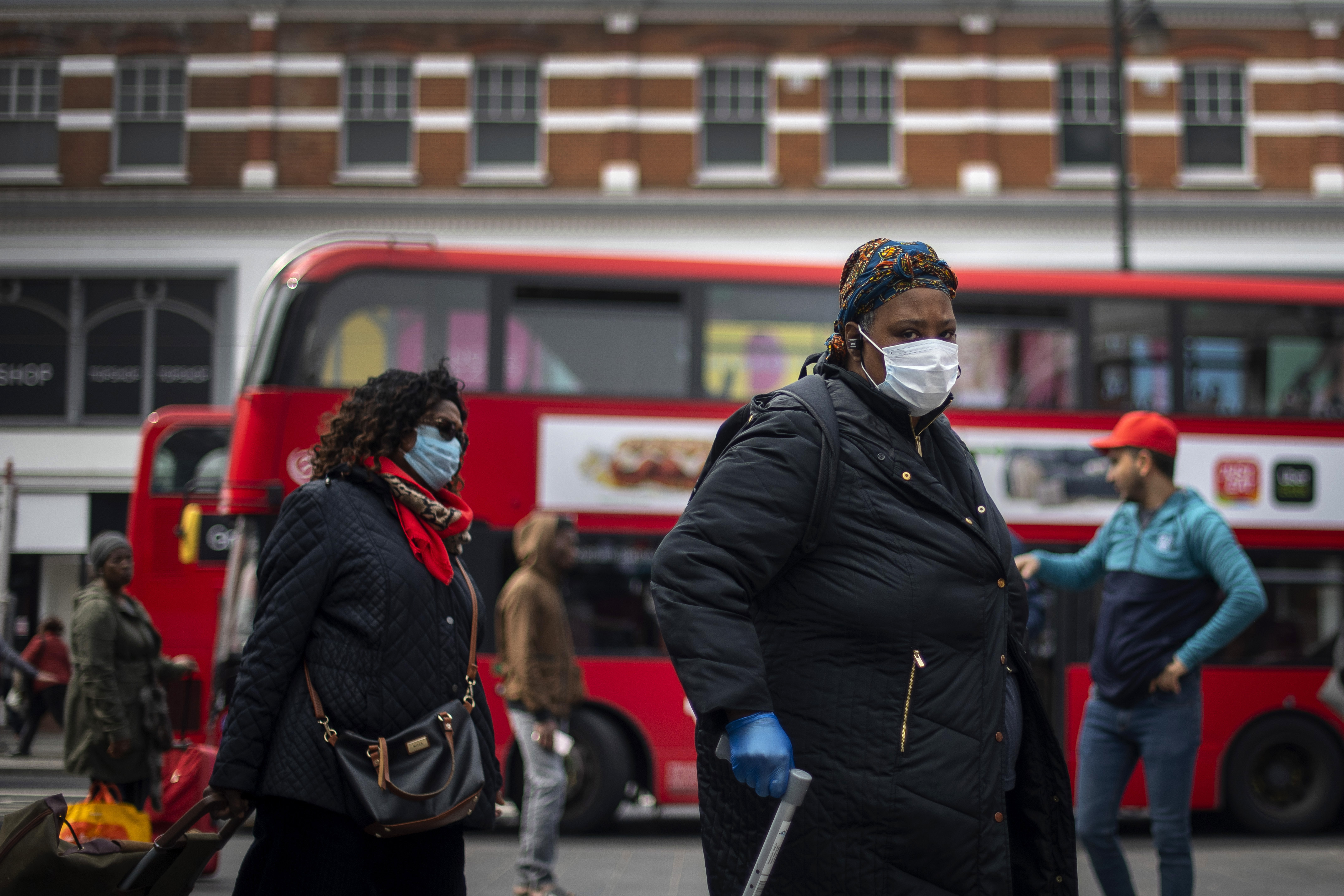 A woman in a protective face mask walks through Brixton Market in South London, as the UK continues in lockdown to help curb the spread of the coronavirus.