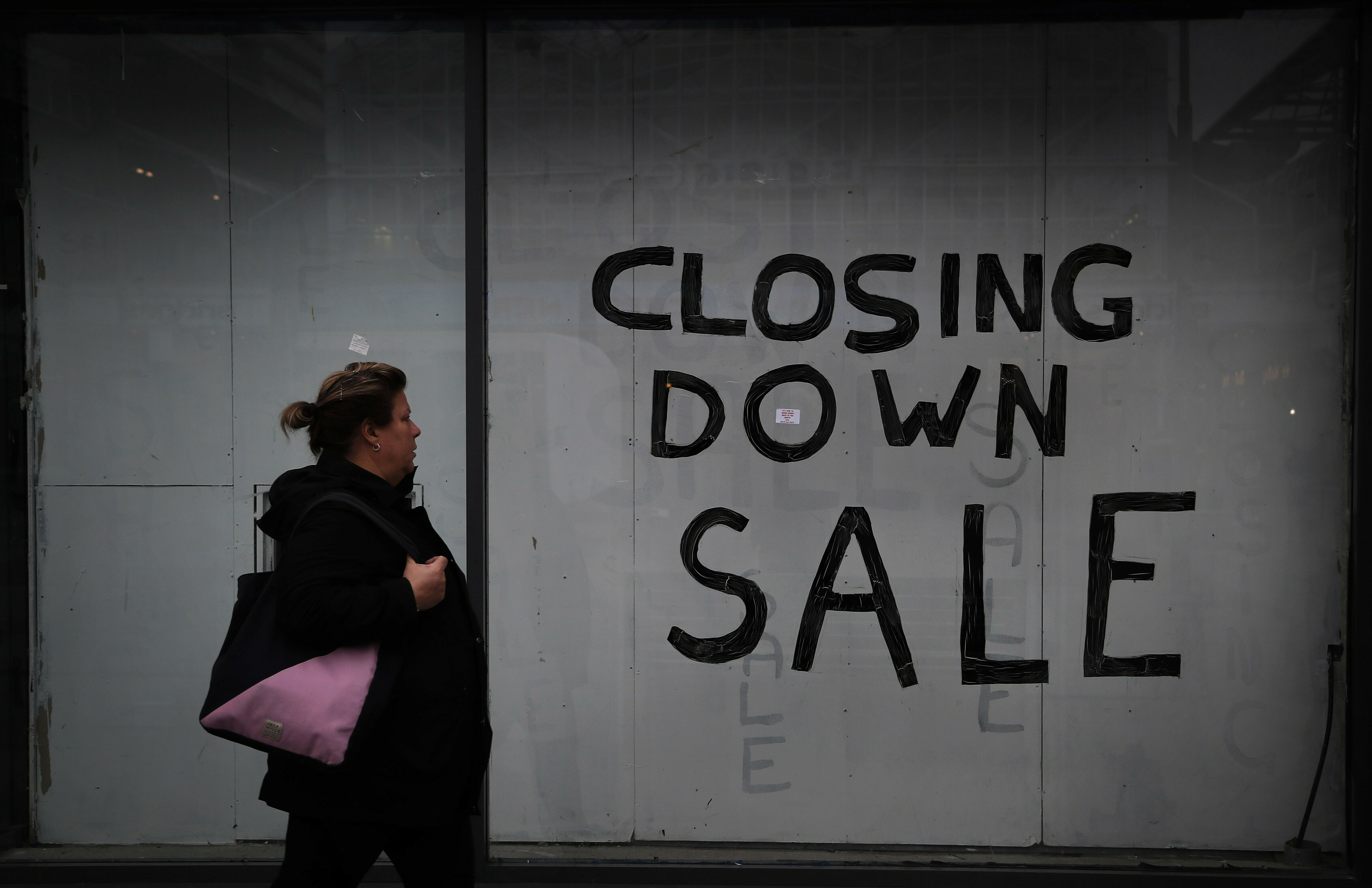 A woman passes a closed down shop in the city centre of Sunderland, England, Wednesday, March 13, 2019. Sunderland voted for Brexit to make itself heard, and in hope of a brighter future. Almost three years later, residents are still waiting. (AP Photo/Frank Augstein)