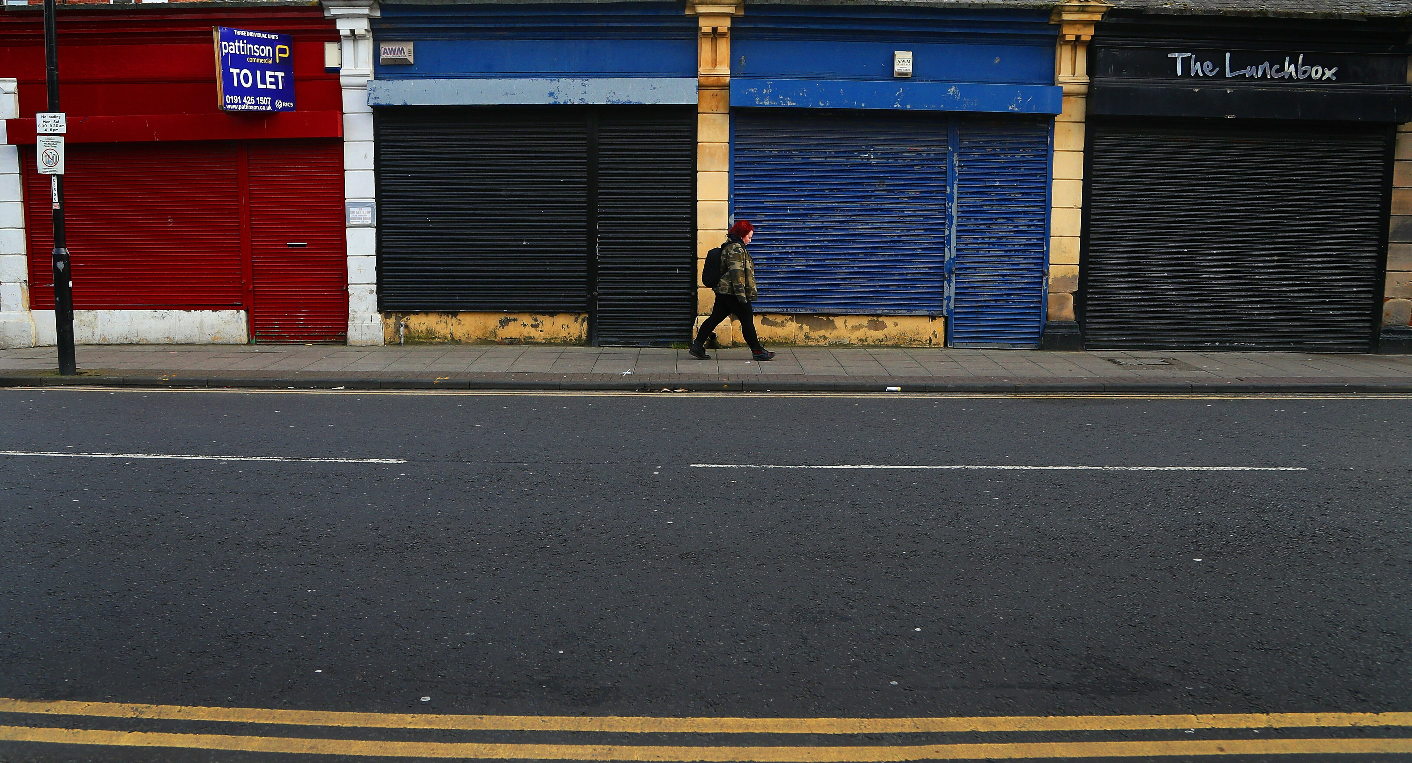 A woman passes closed down shops in the city centre of Sunderland, England, Wednesday, March 13, 2019. The city's unemployment rate is well above the national average, and pockmarked and shuttered buildings with broken windows scar its landscape. Renewal has been made harder by years of public-spending cuts under a deficit-slashing British government.(AP Photo/Frank Augstein)