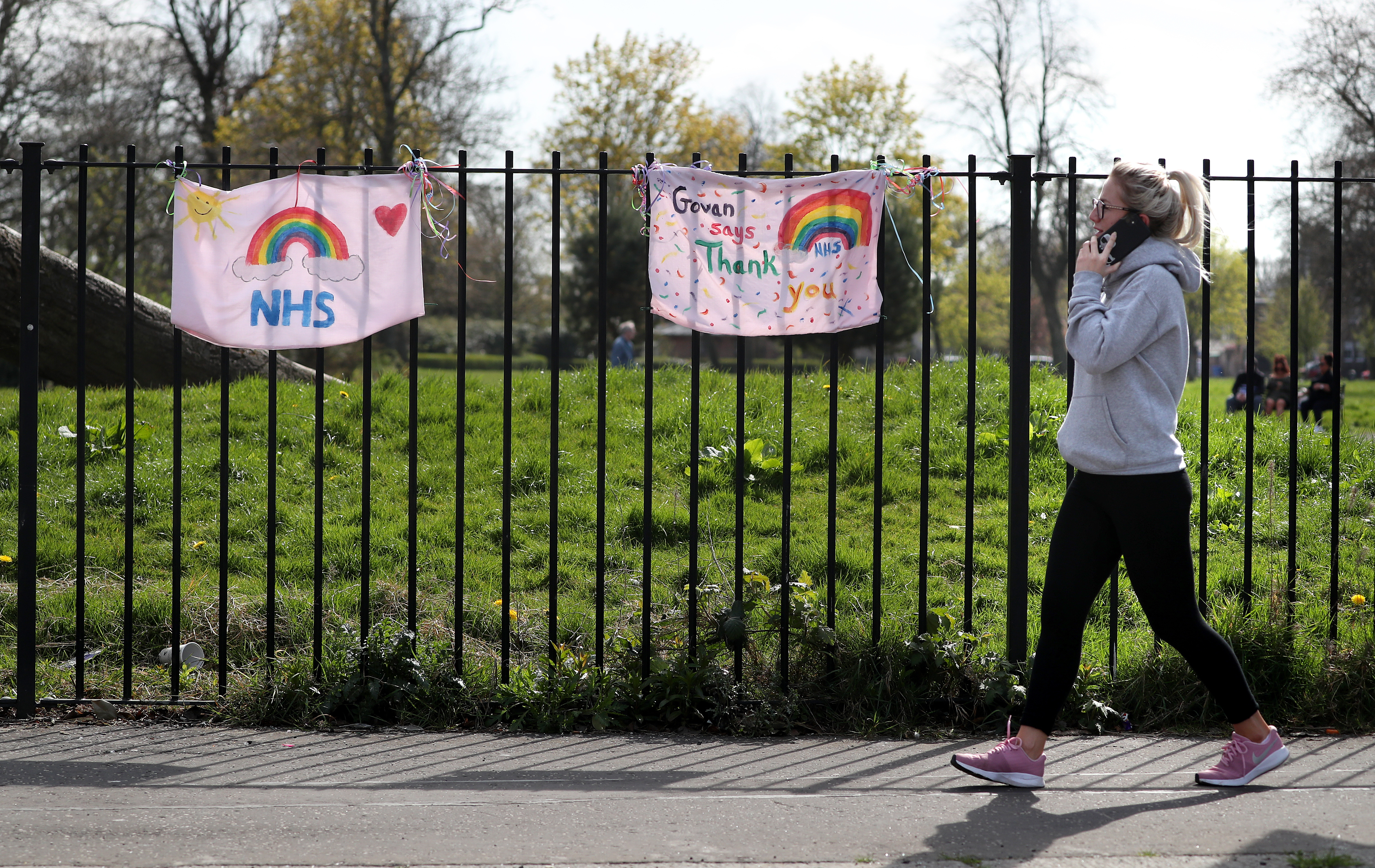 A woman walks past NHS tributes which are painted on pillow cases attached to the fence at Elder Park in Glasgow as the UK continues in lockdown to help curb the spread of the coronavirus.